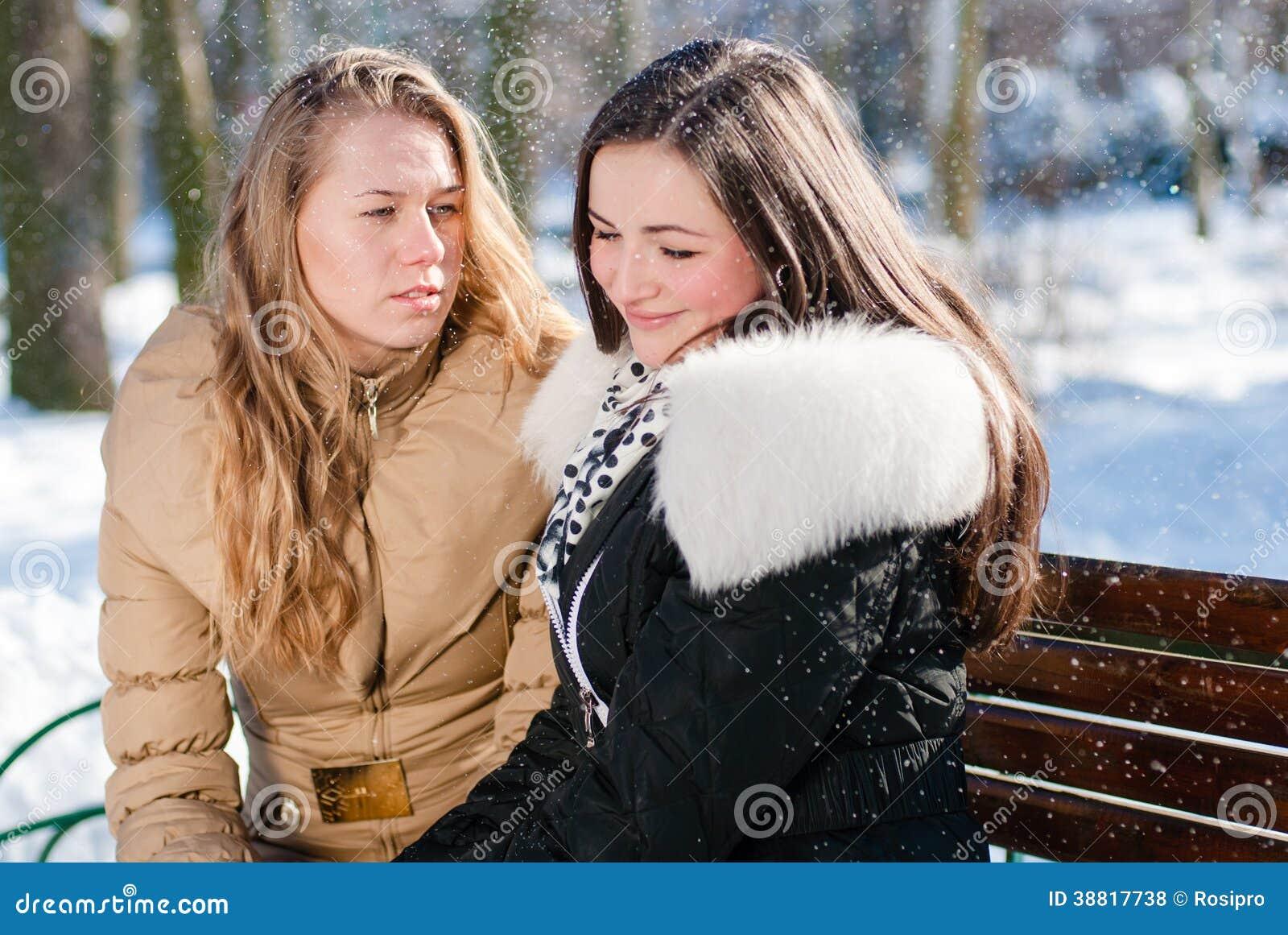 2 junge schöne hübsche Frauen, die auf einer Bank im Winter sitzen, parken draußen