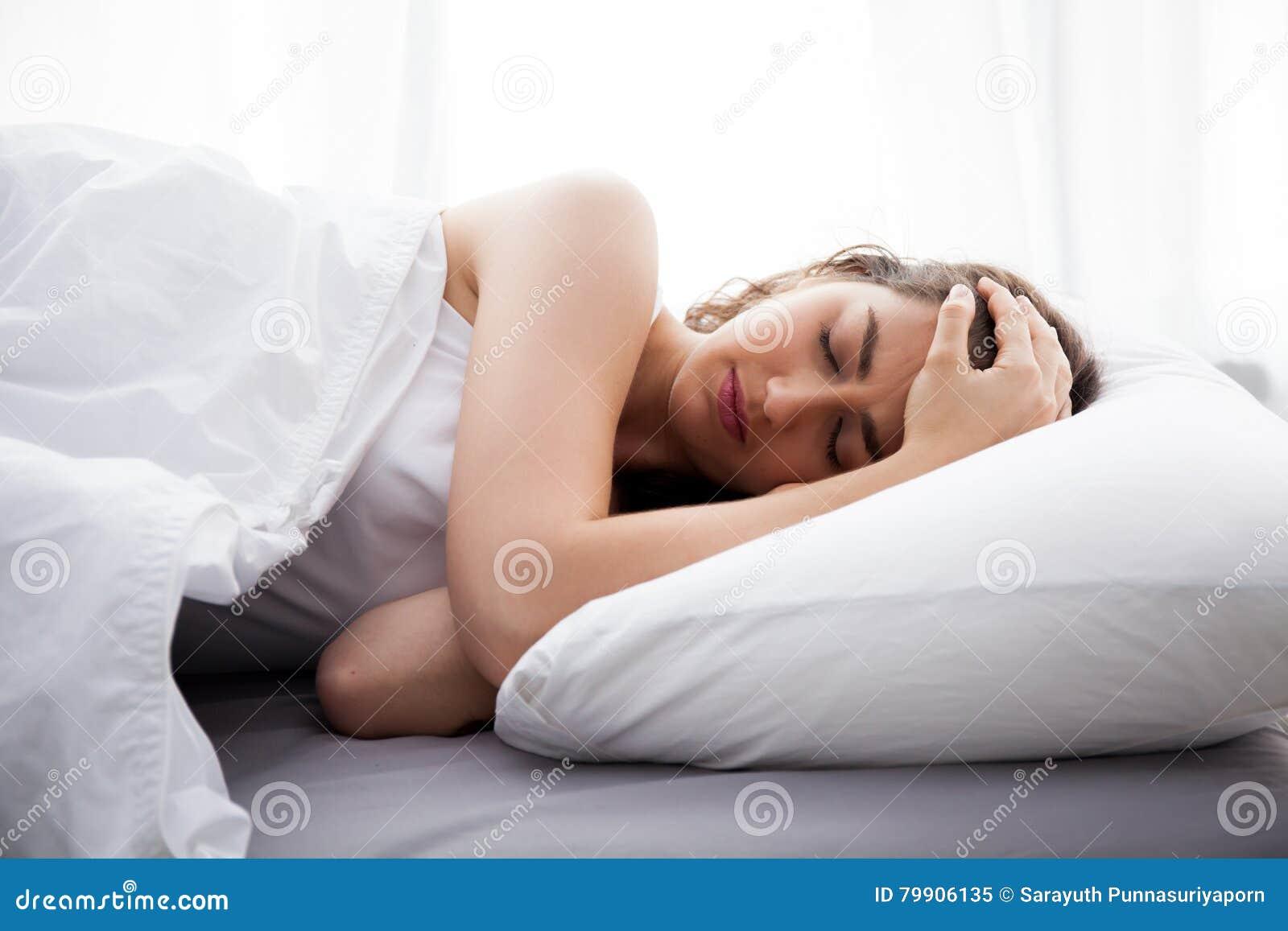 Junge schöne kaukasische Frau auf dem Bett, das Kopfschmerzen/Schlaflosigkeit/Migräne/Druck hat