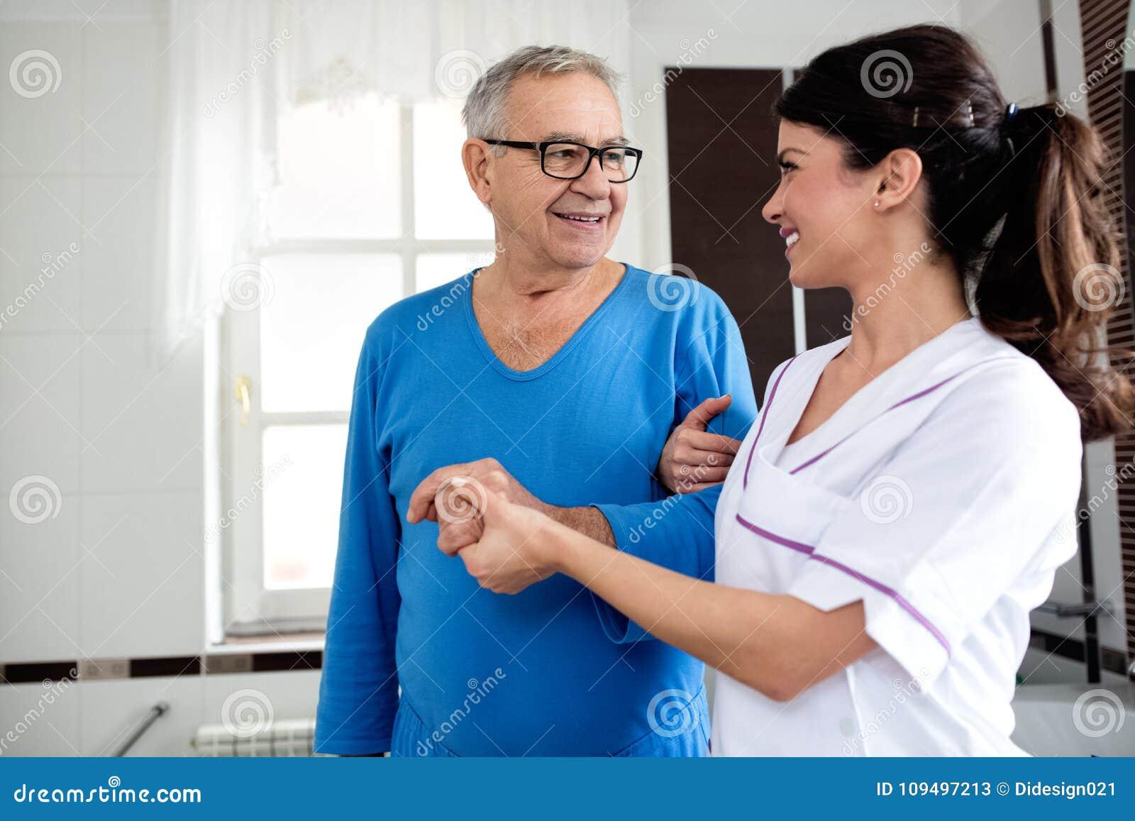 Junge schöne Krankenschwester hilft zum älteren Mann am Badezimmer