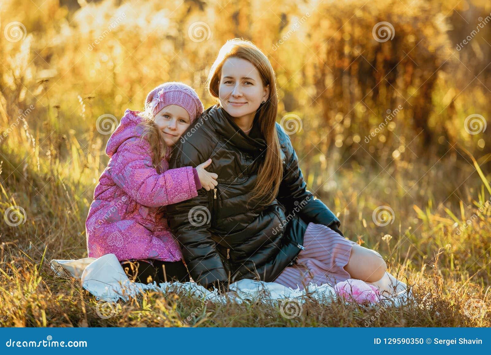 Junge schöne Mutter mit ihrer Tochter auf einem Weg an einem sonnigen Herbsttag Sie sitzen auf einem Plaid auf dem Gras, eine Toc