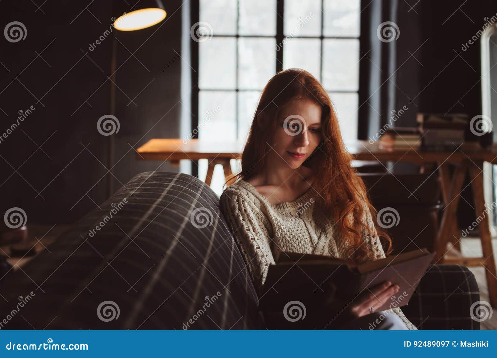 junge sch ne rothaarigefrau die sich zu hause im gem tlichen abend und lesebuch des herbstes. Black Bedroom Furniture Sets. Home Design Ideas