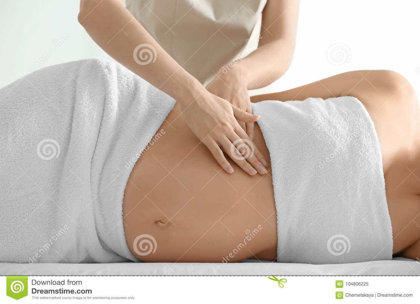 Junge schöne schwangere Frau, die Massage hat