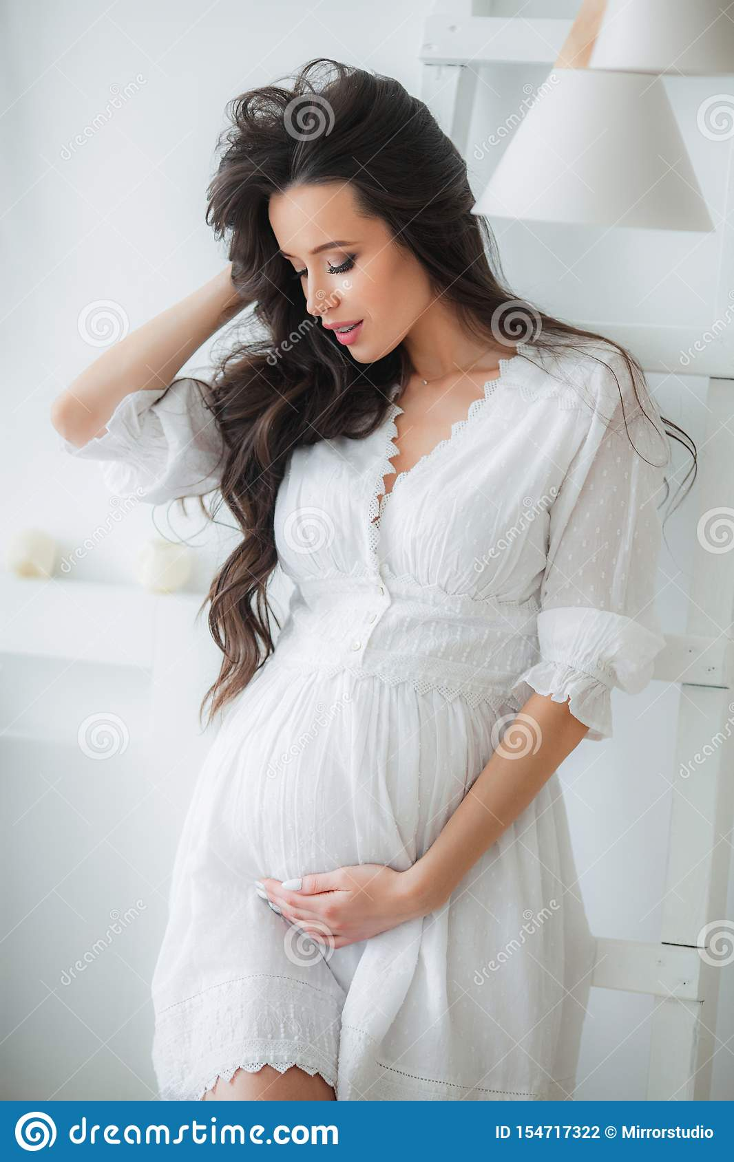 junge schöne schwangere frau im weißen kleid stockfoto