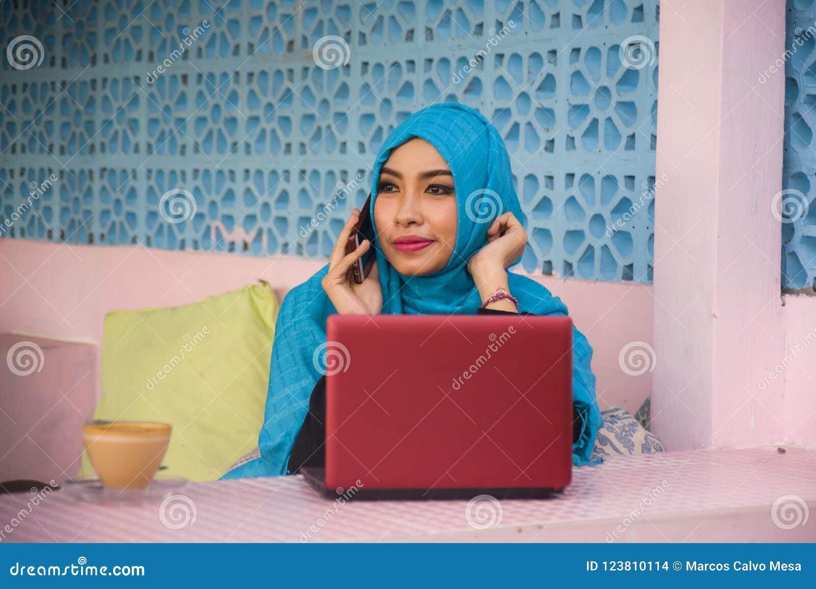 Junge schöne und glückliche Frau in moslemischem hijab Kopftuch, das mit Laptop-Computer und Handydem vernetzungslaufen Inter- ar