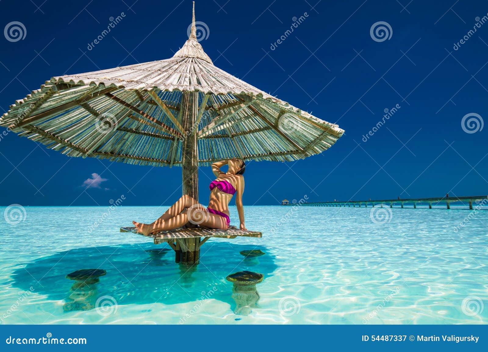 Junge Schönheit in den Bikinis unter Strandschirm im oce