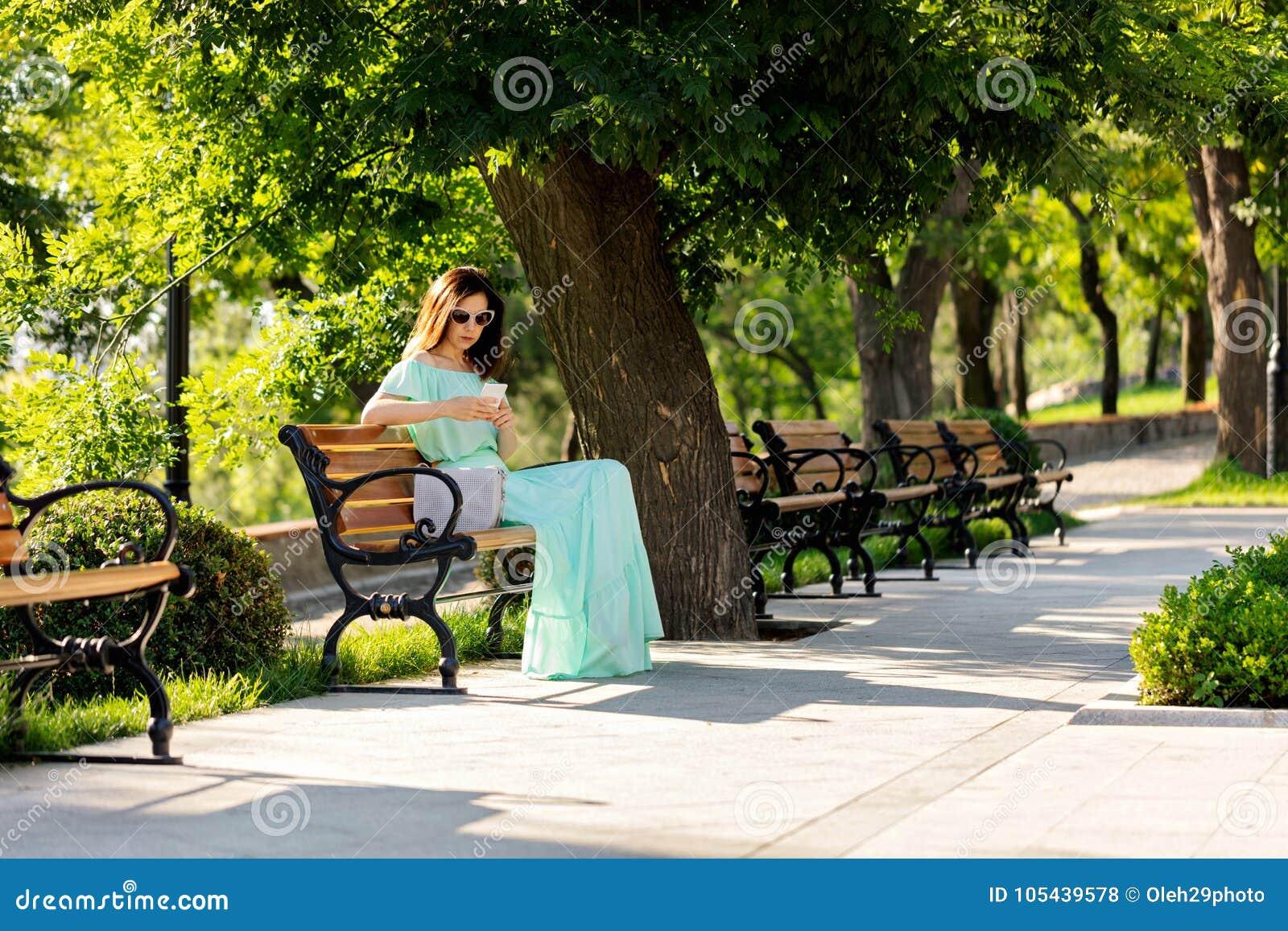 Junge Schönheit in einem hellgrünen langen Pastellkleid ist sitt