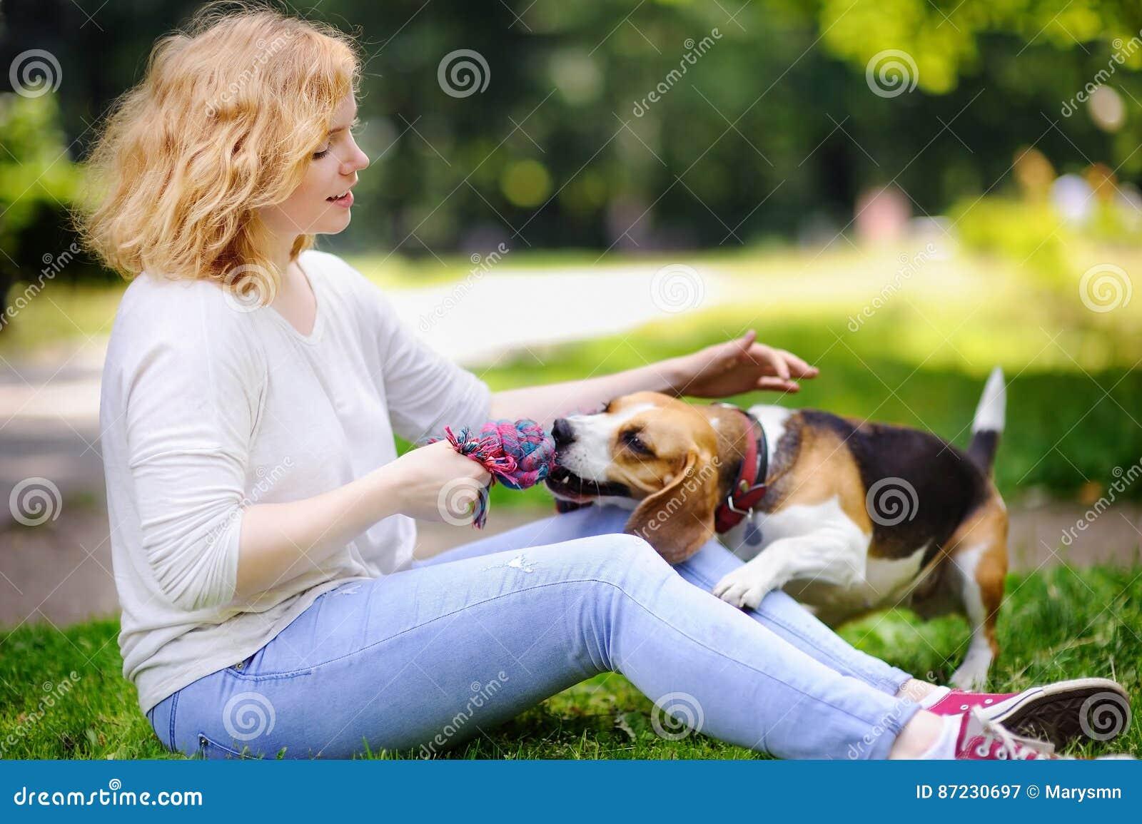 Junge Schönheit mit Spürhundhund im Sommerpark