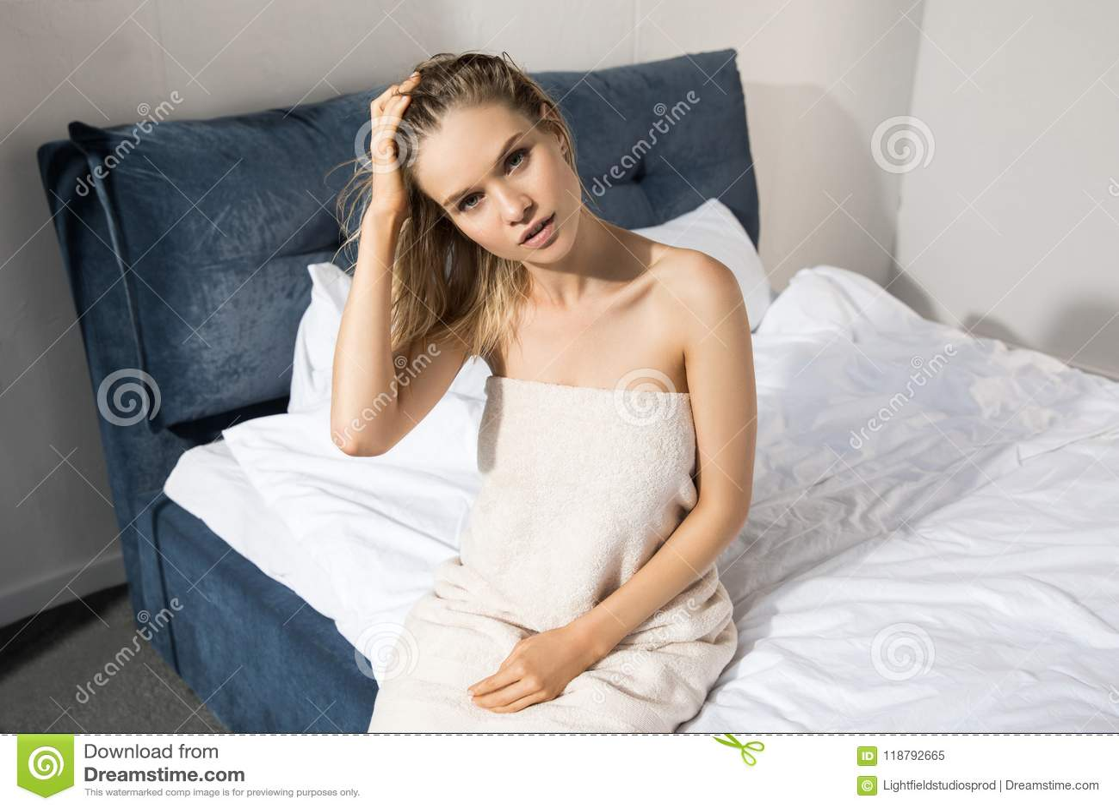 Junge Schönheit oben eingewickelt mit dem Badtuch, das auf Bett und dem Schauen sitzt