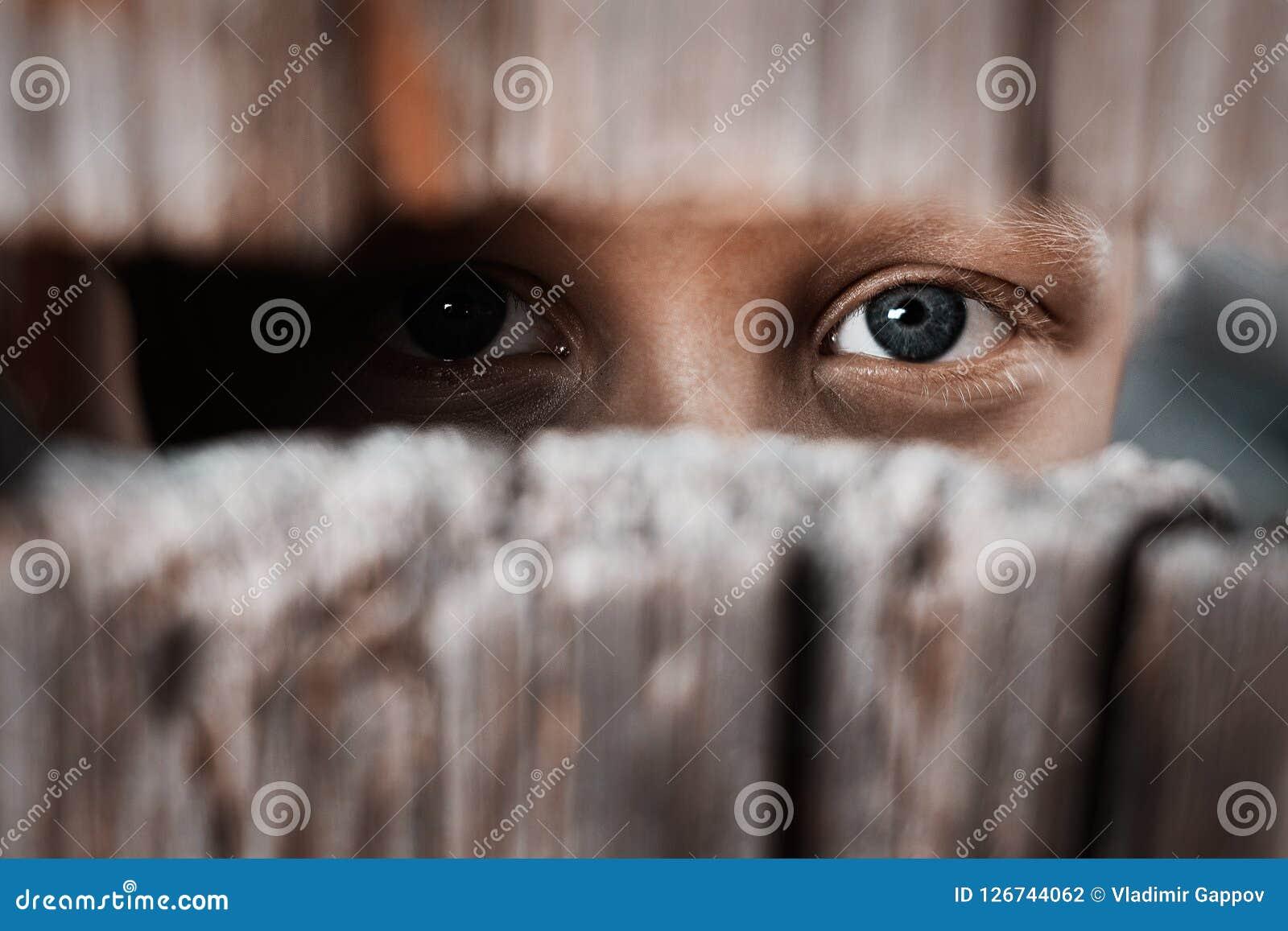 Junge schaut durch den Abstand im Zaun Das Konzept von Voyeurism, von Neugier, von Jäger, von Überwachung und von Sicherheit
