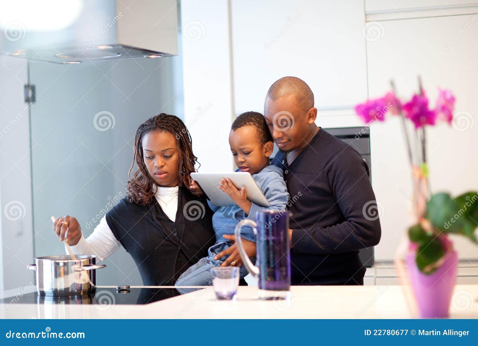 Junge schwarze Familie in der frischen modernen Küche