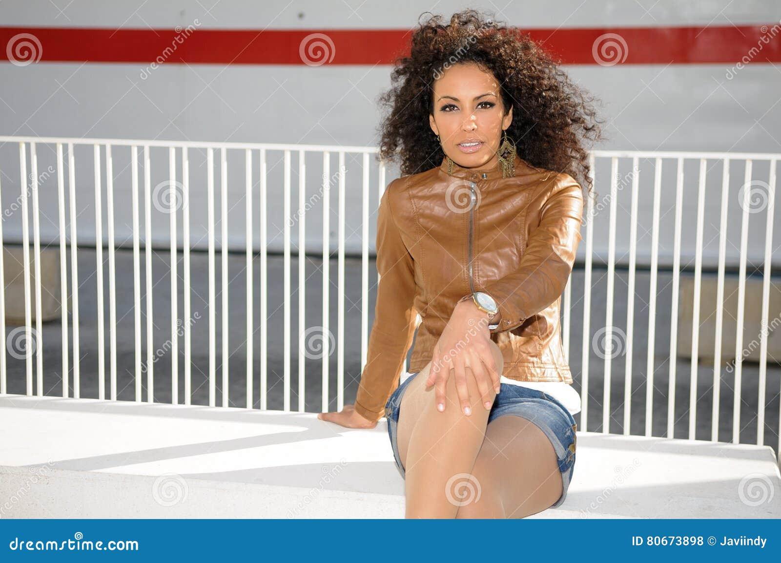 Junge schwarze Frau, Afrofrisur, im städtischen Hintergrund