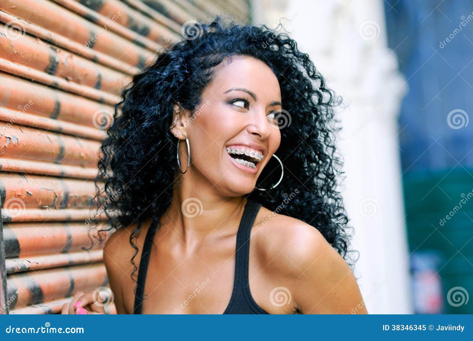 Junge schwarze Frau, die mit Klammern lächelt