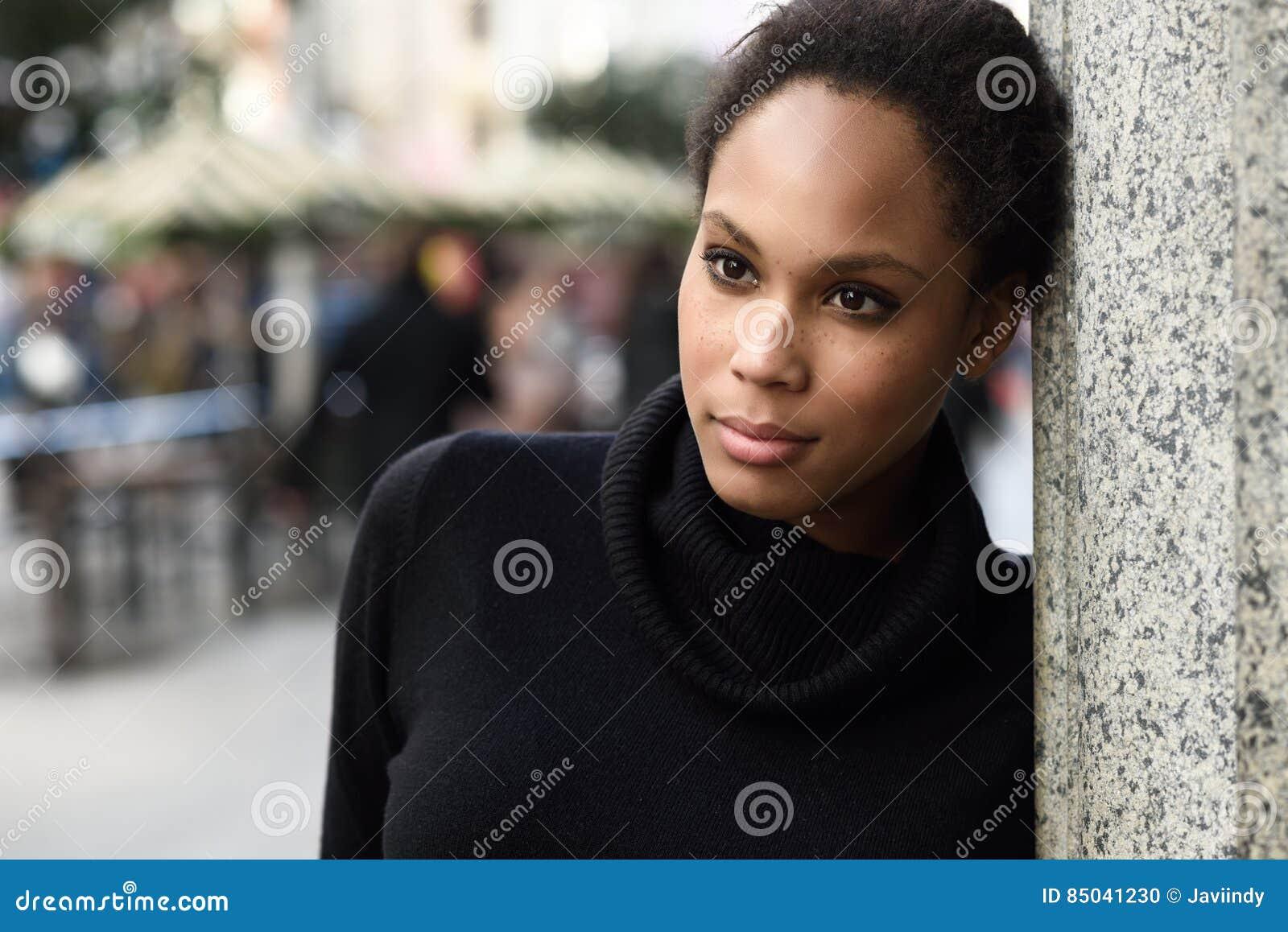 Junge schwarze Frau mit der Afrofrisur, die im städtischen backgrou steht