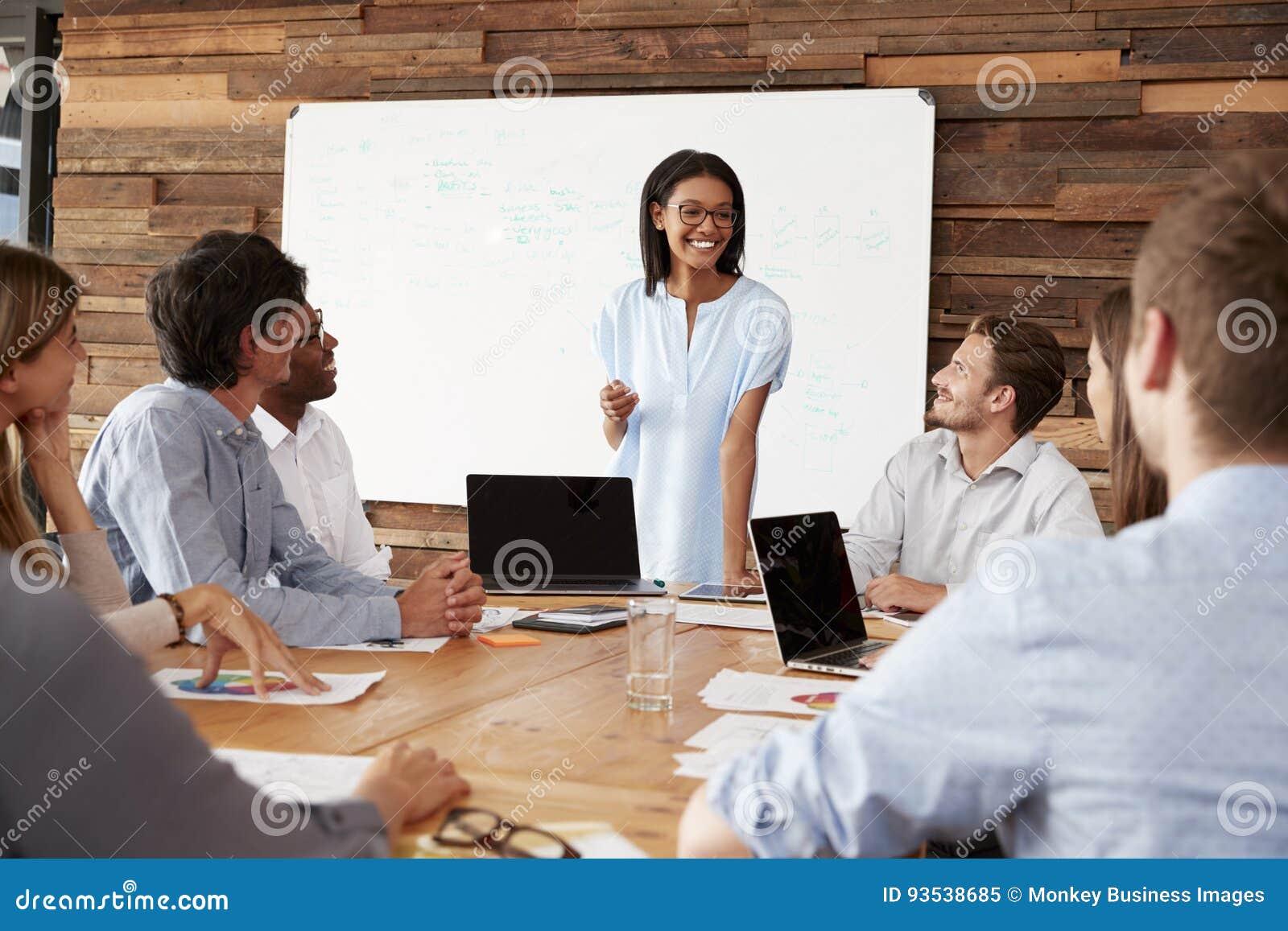 Junge schwarze Frau steht, sprechend zu Kollegen bei einer Sitzung