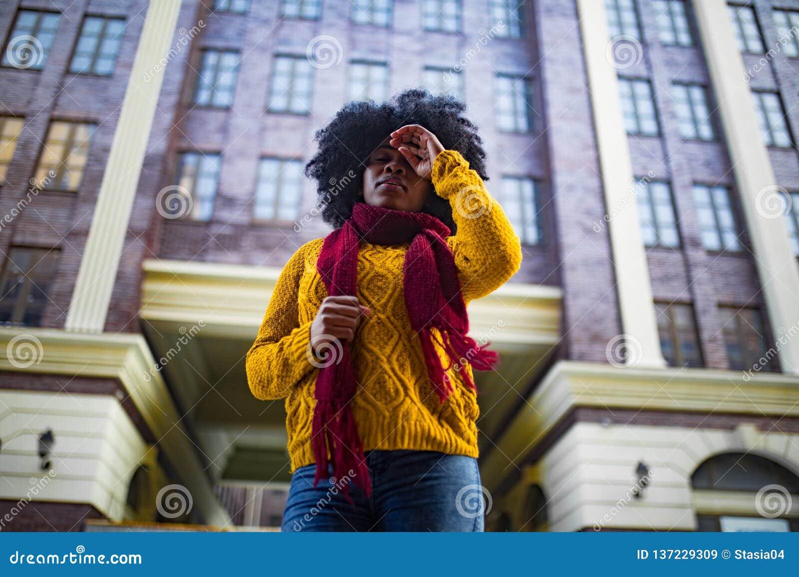 Junge schwarze traurige Frau steht gegen Hintergrund des Gebäudes
