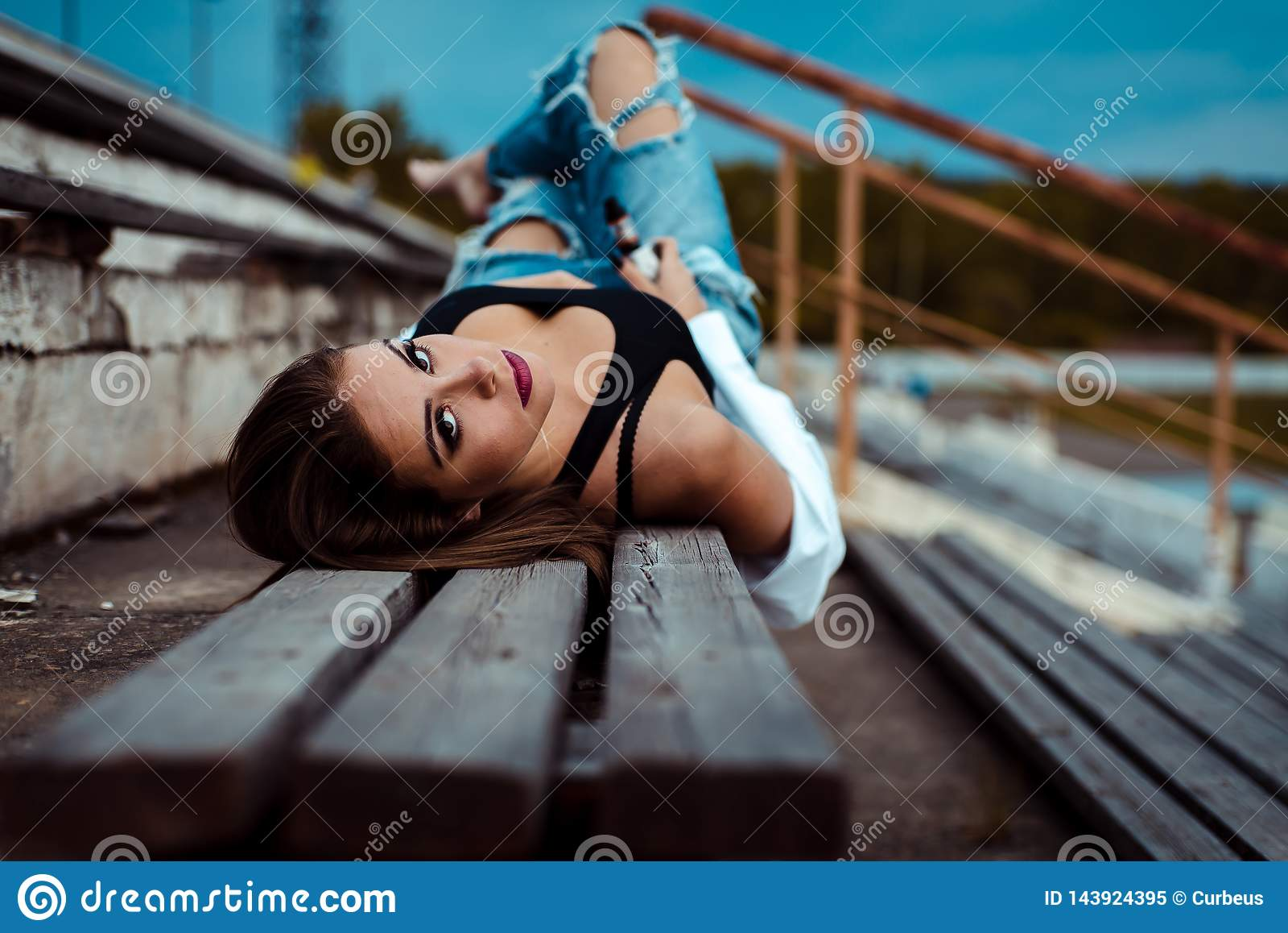 Junge sexy Frau liegt auf einer Holzbank Sie macht Pause nach Training in der Turnhalle outdoor
