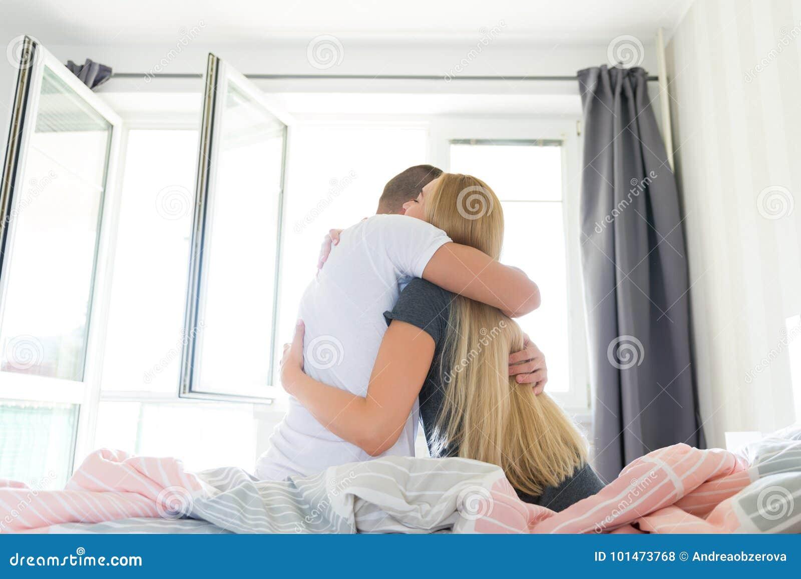 Junge sexy Paare, nachdem morgens aufwachen, sitzend auf dem Bett und umarmen