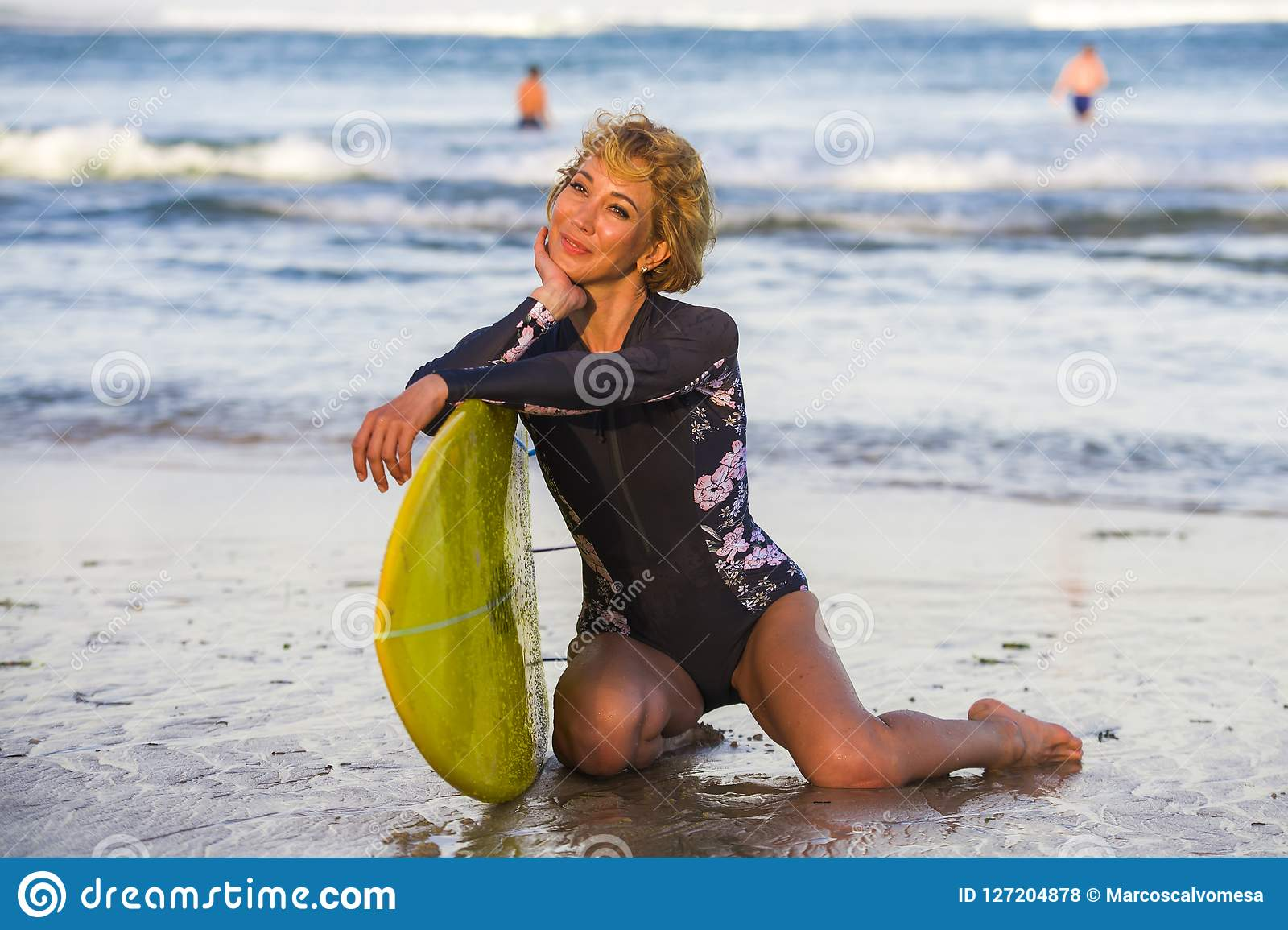 Junge sexy schöne und glückliche Surferfrau, die auf dem Strandsand hält gelbes lächelndes nettes genießendes holid Sommer des Br