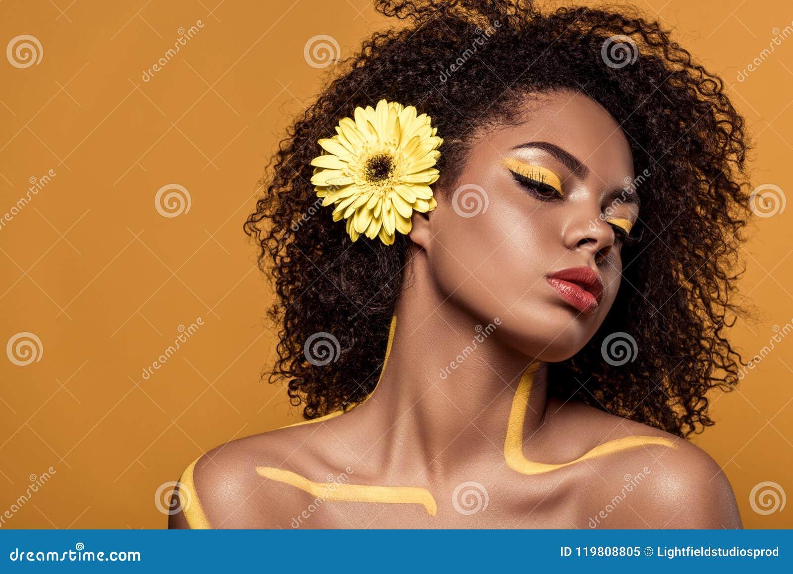 Junge sinnliche Afroamerikanerfrau mit künstlerischem Make-up und Gerbera im Haar