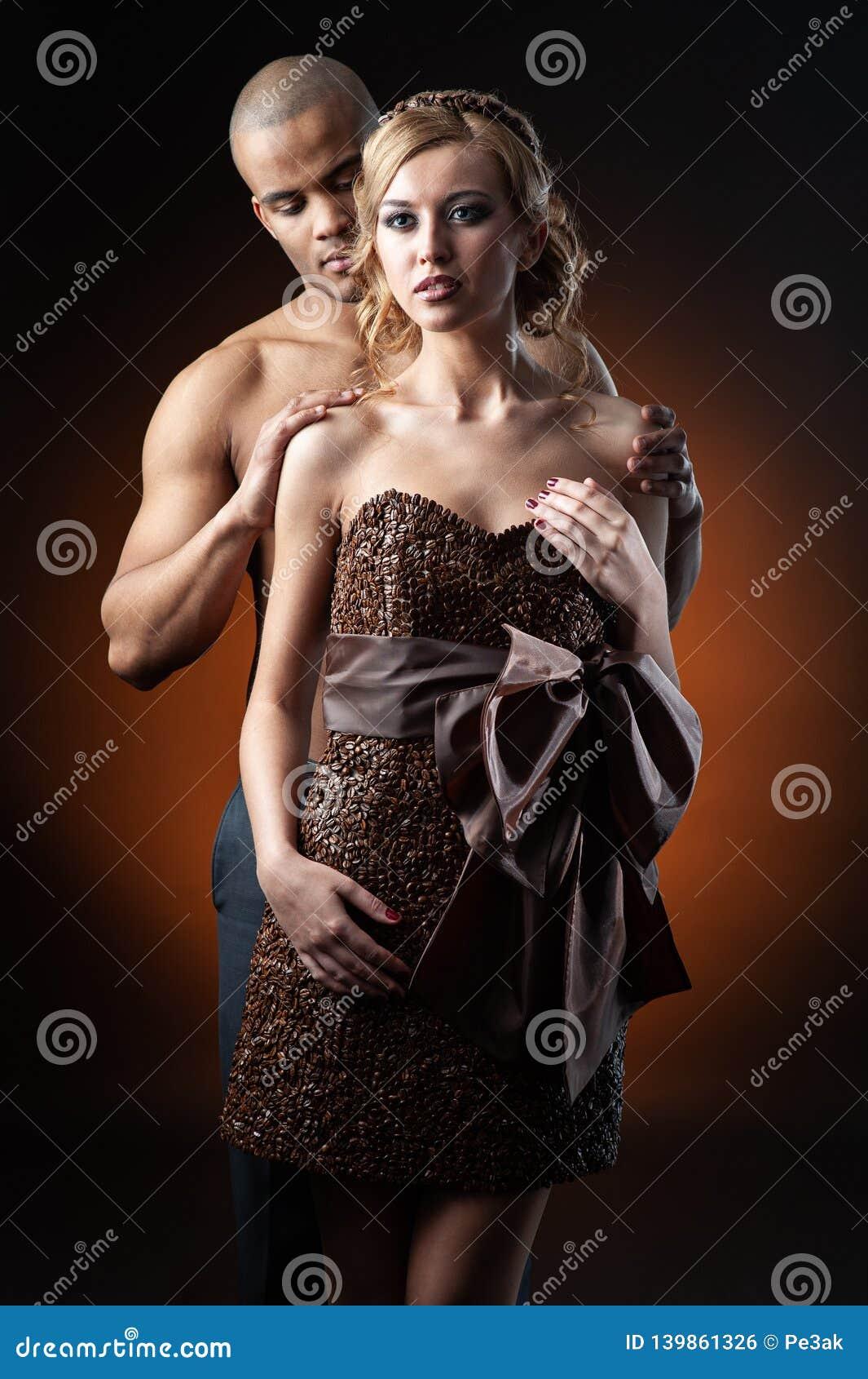 Junge sinnliche kaukasische Frau im Kleid hergestellt von der Stellung der Kaffeebohnen und des schwarzen Mannes über orange Hint