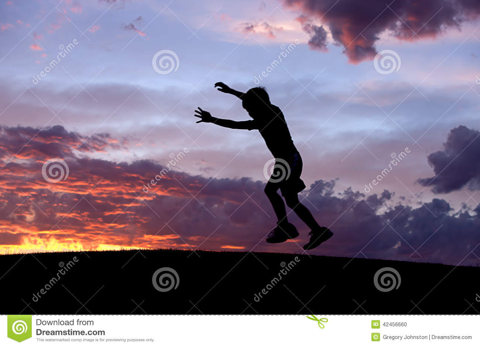 Junge springt bei Sonnenuntergang
