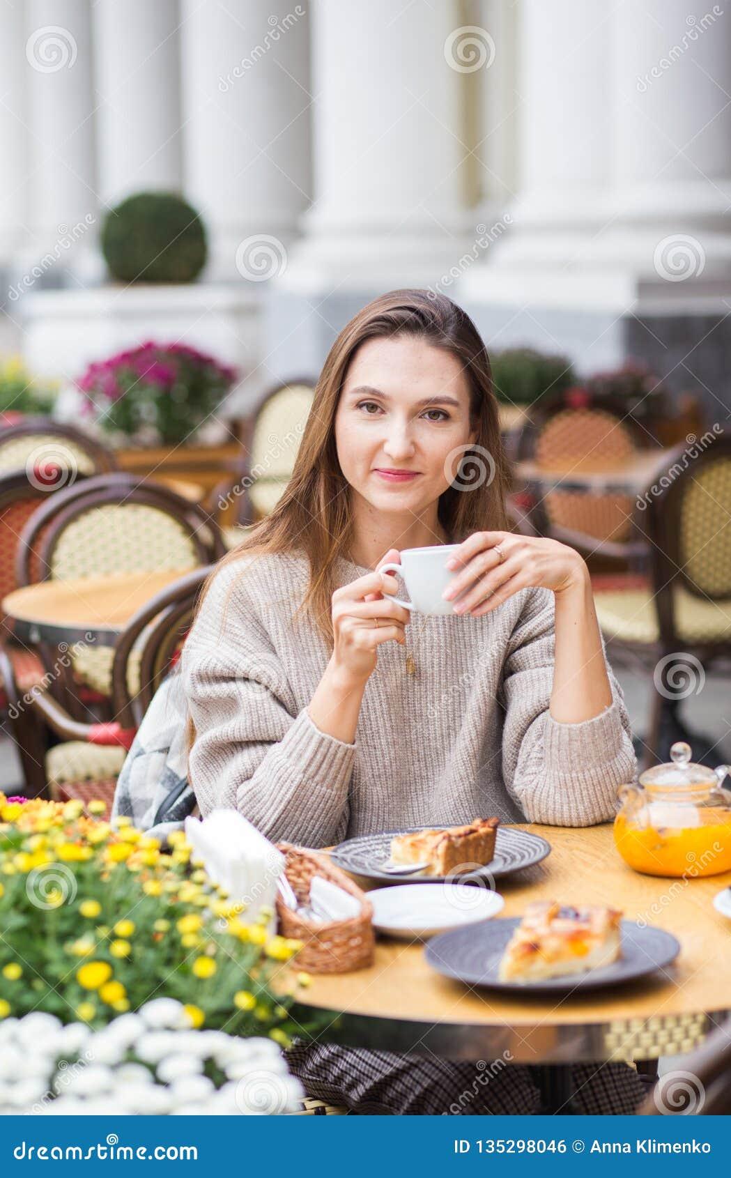 Junge stilvolle Frau, die französisches mit dem Kaffee und Kuchen sitzen an der Caféterrasse frühstückt