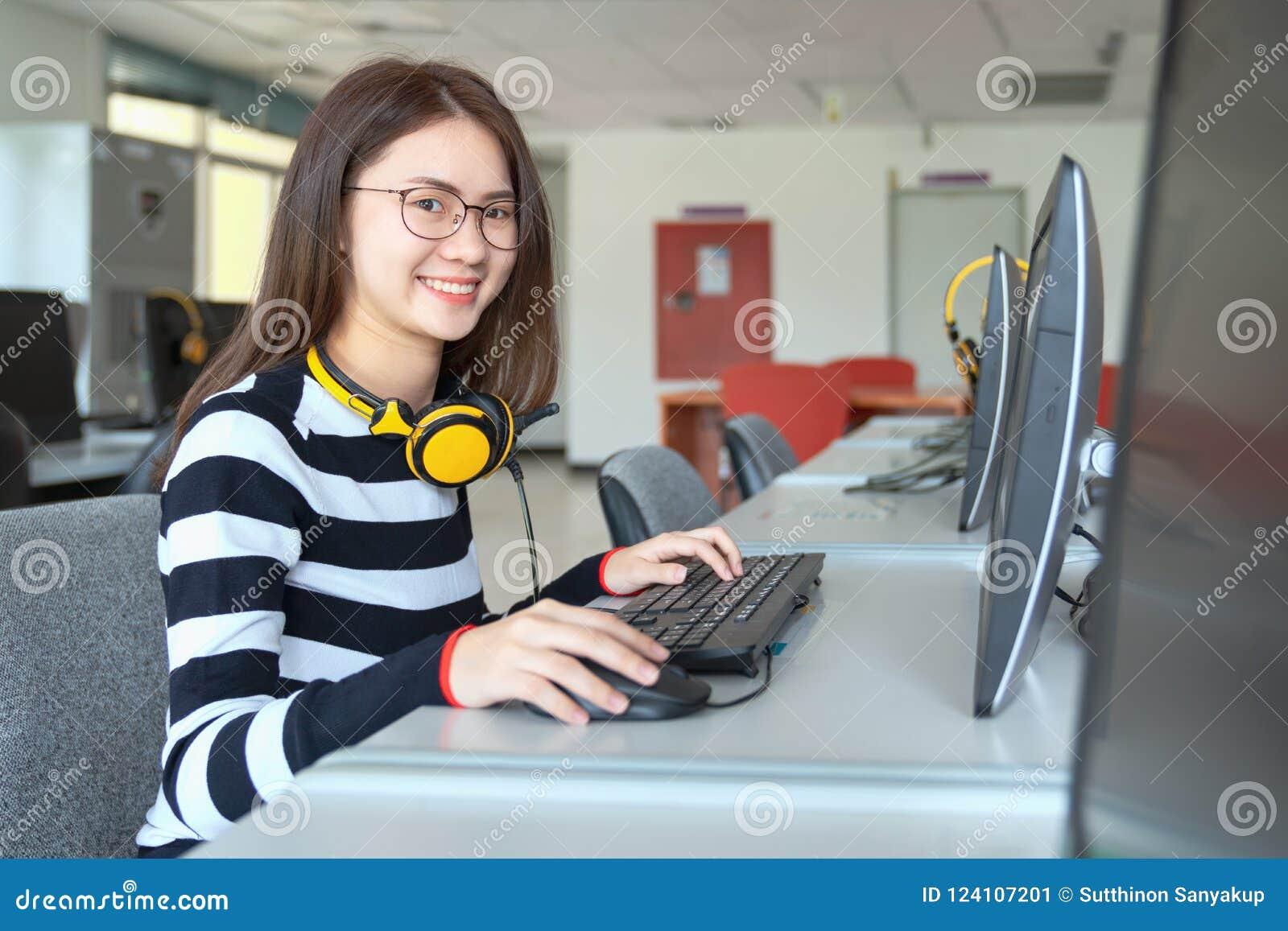 Junge Studentinstudie in der Schulbibliothek, sie unter Verwendung des Laptops und online lernen, zurück zu Schulbildungswissensc