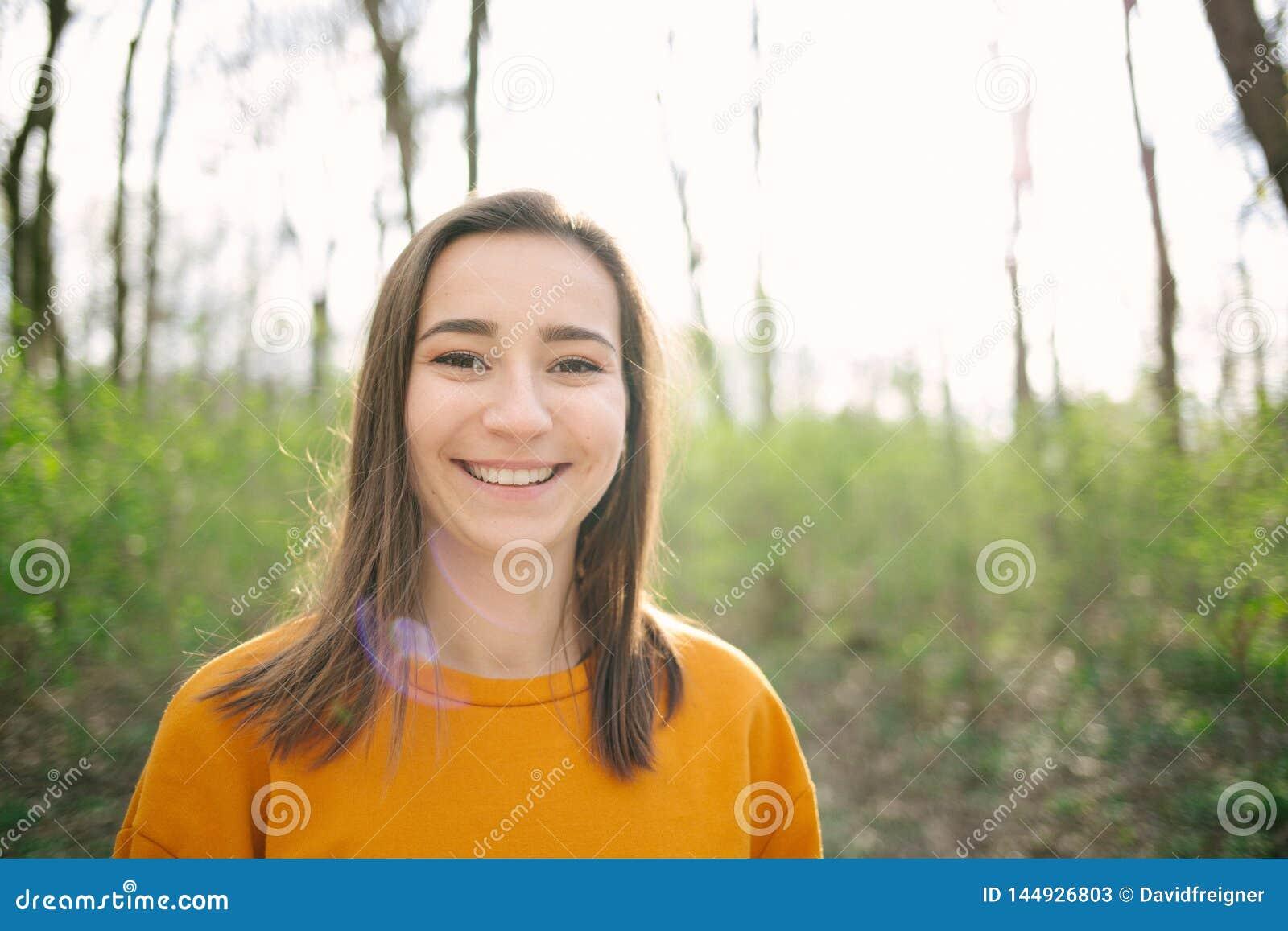 Junge und attracive Frauenstellung und im Wald lachen
