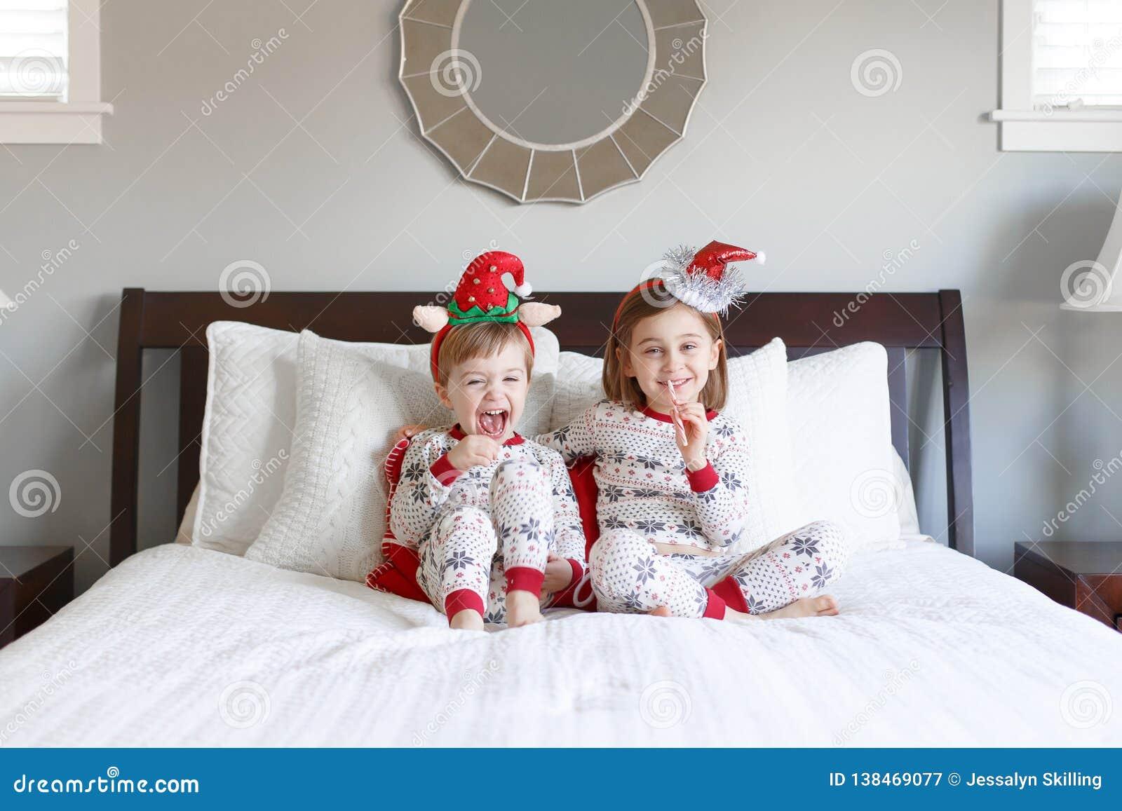 Junge und Mädchen auf Bett mit Weihnachtspyjamas