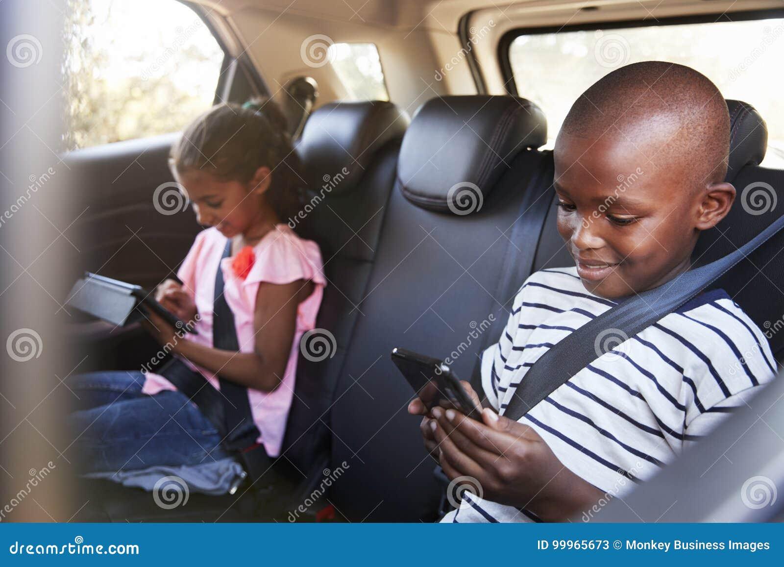 Junge und Mädchen in einem Auto unter Verwendung der Tablette und des Smartphone auf einer Reise