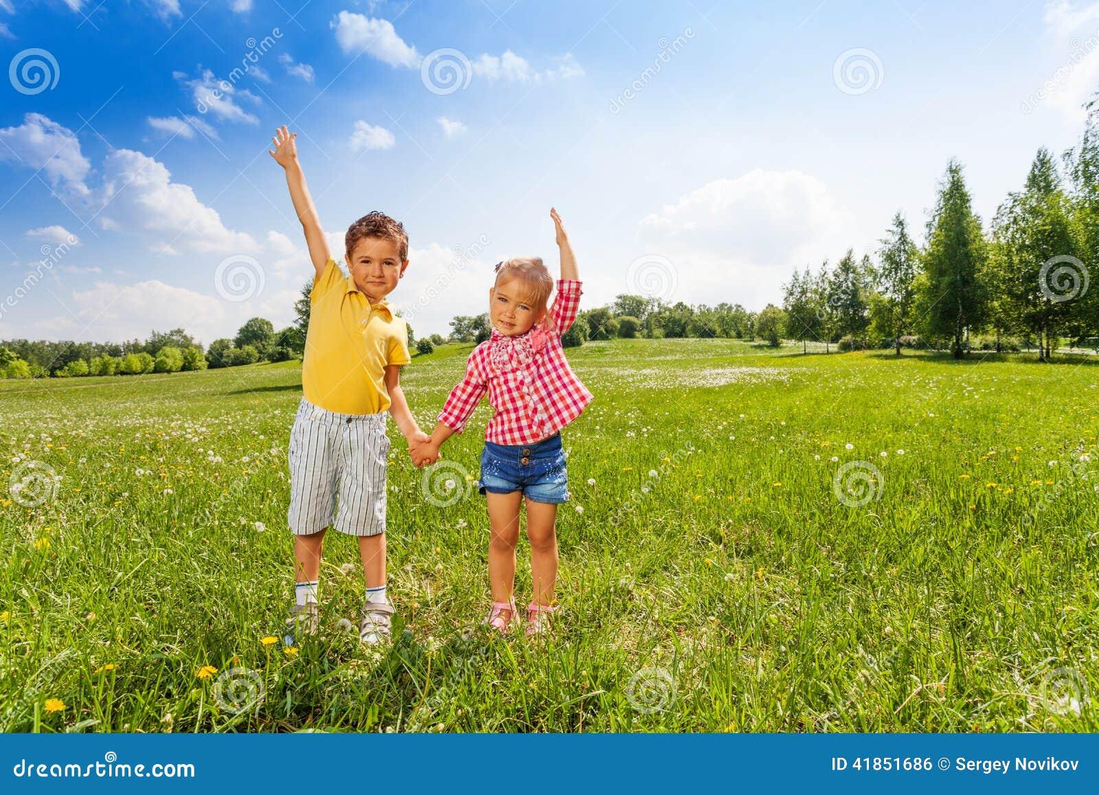 Junge Und Mädchen Halten Hände Mit Der Zweiten Hand Oben Stockfoto ...