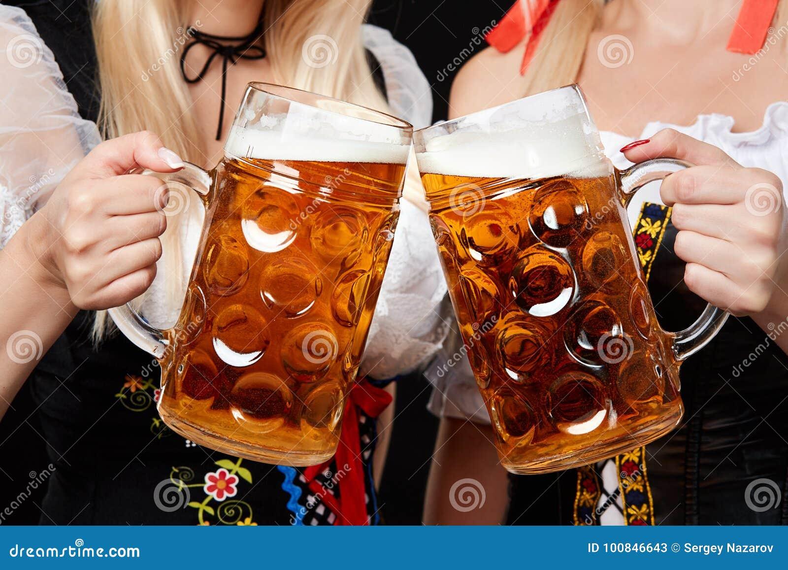 Junge und schöne bayerische Mädchen mit zwei Bierkrügen auf schwarzem Hintergrund