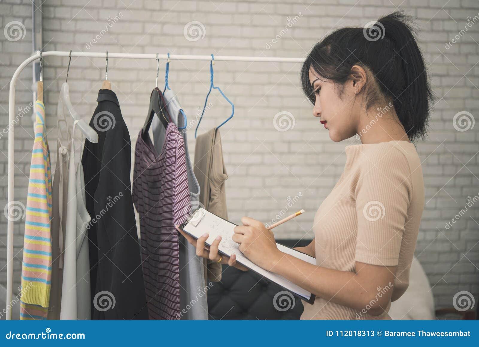 Junge weibliche Designermode, die für Näherinkleid arbeitet