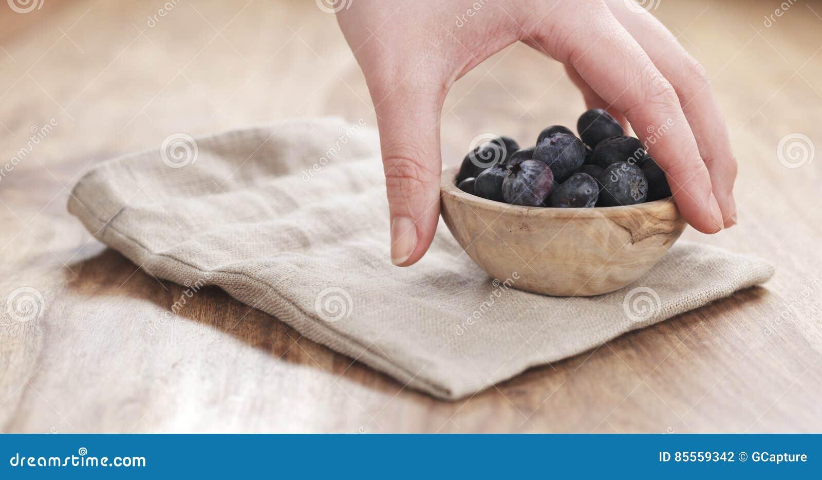 Junge weibliche Hand, die Schüssel Blaubeeren auf Tabelle setzt