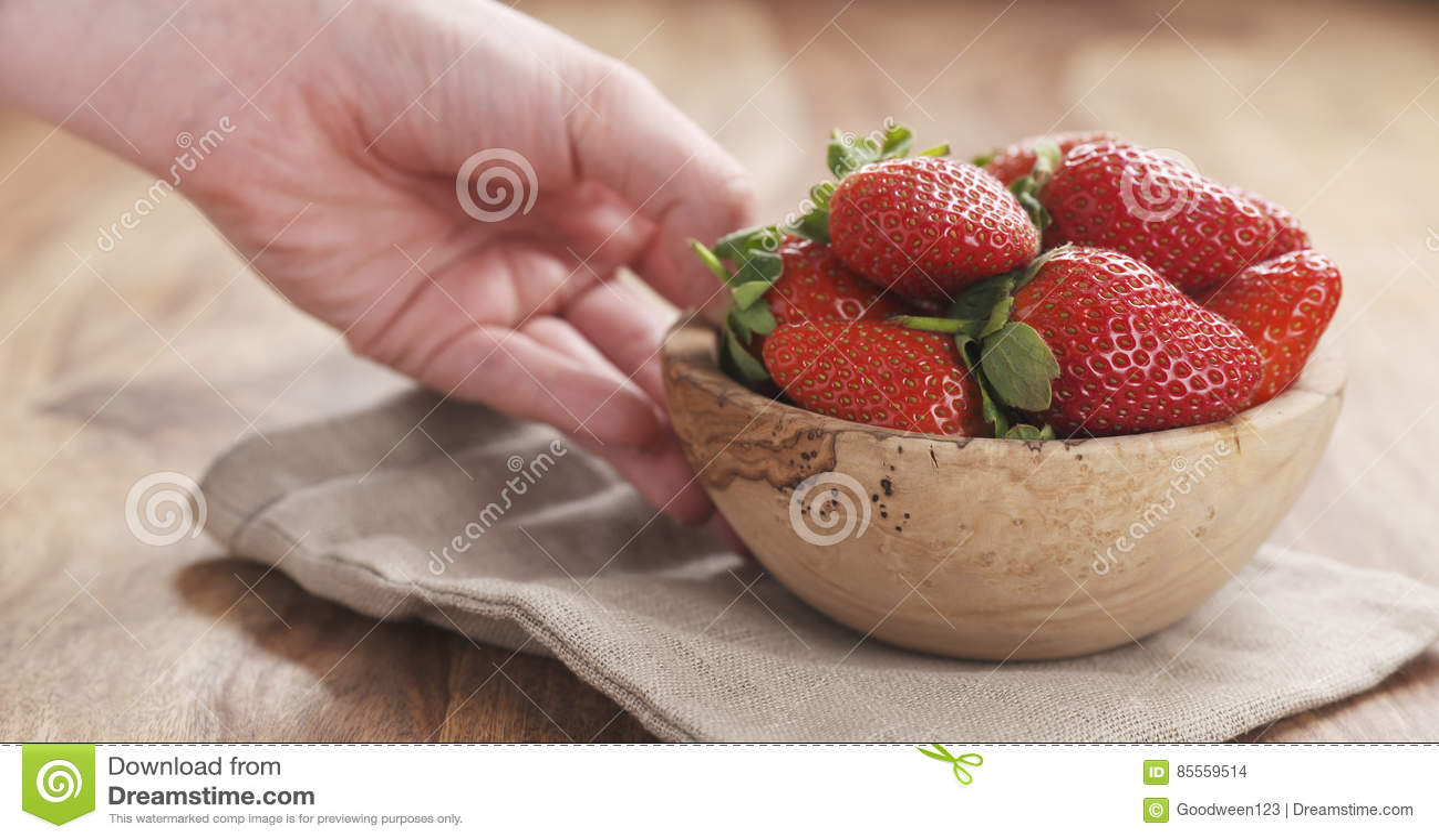 Junge weibliche Hand setzt Schüssel Erdbeeren auf Tabelle