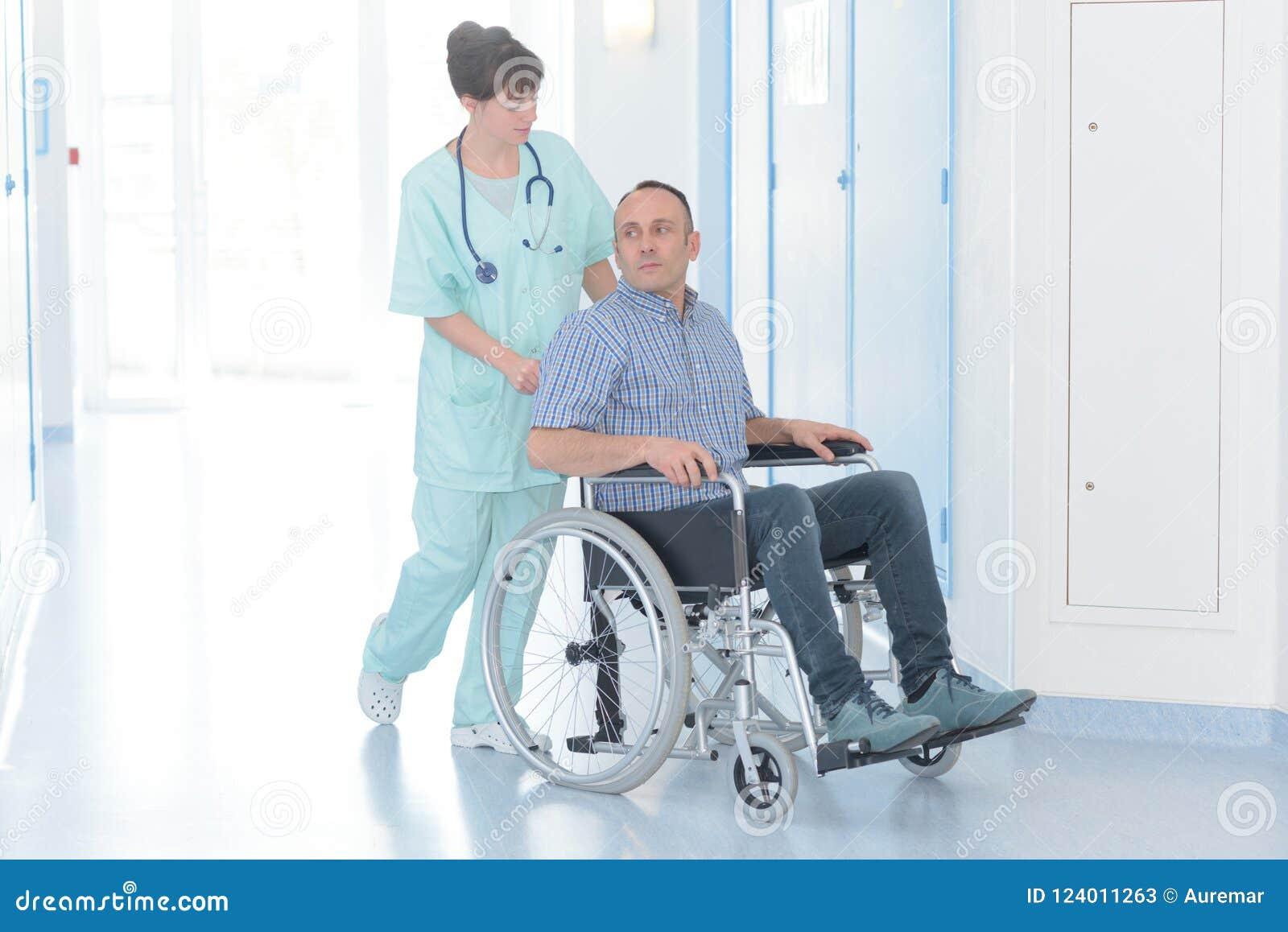 Junge weibliche Krankenschwester mit behindertem männlichem Patienten auf Rollstuhl