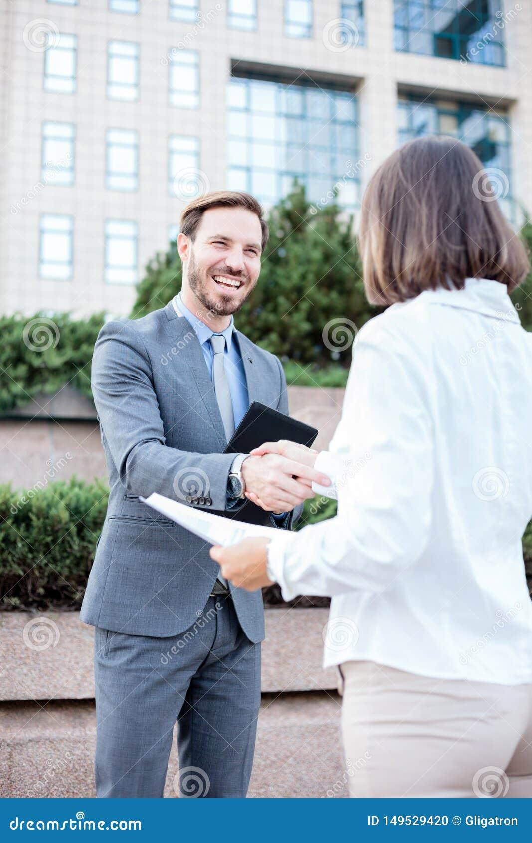 Junge weibliche und männliche Geschäftsleute, die Hände nach einer erfolgreichen Sitzung vor einem Bürogebäude rütteln