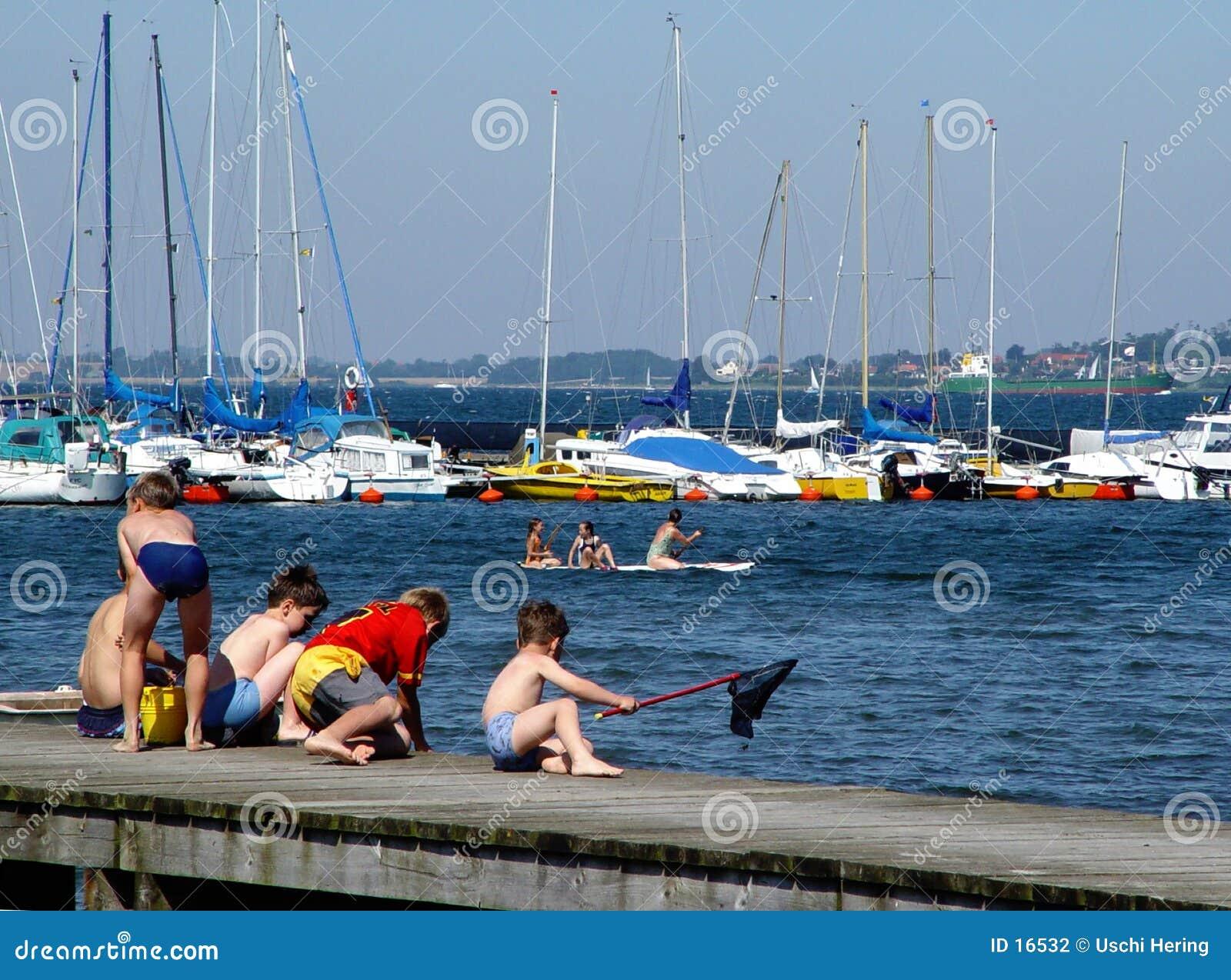 Jungen, die auf einem Pier fischen