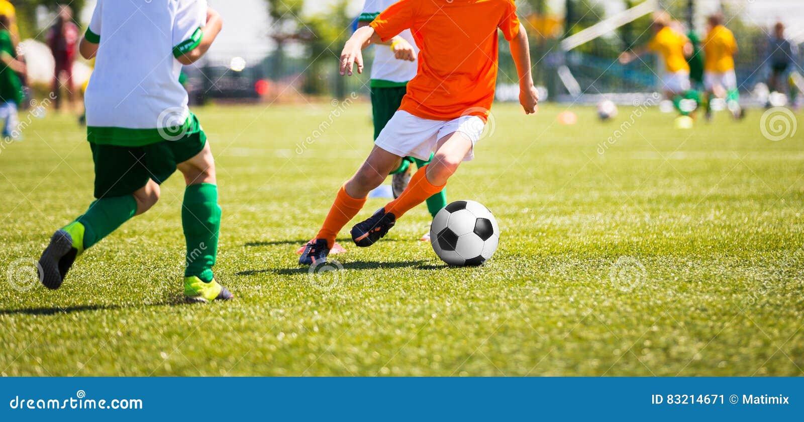 Jungen, die Fußball treten Kinderfußballteam Laufende Fußballspieler