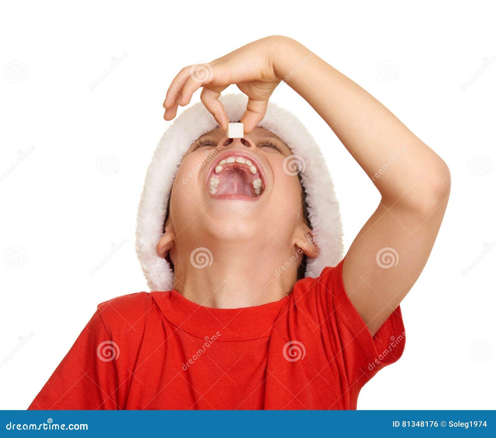 Jungenkind essen Zucker in Sankt-Hut und haben Spaß und Gefühle, Winterurlaubkonzept