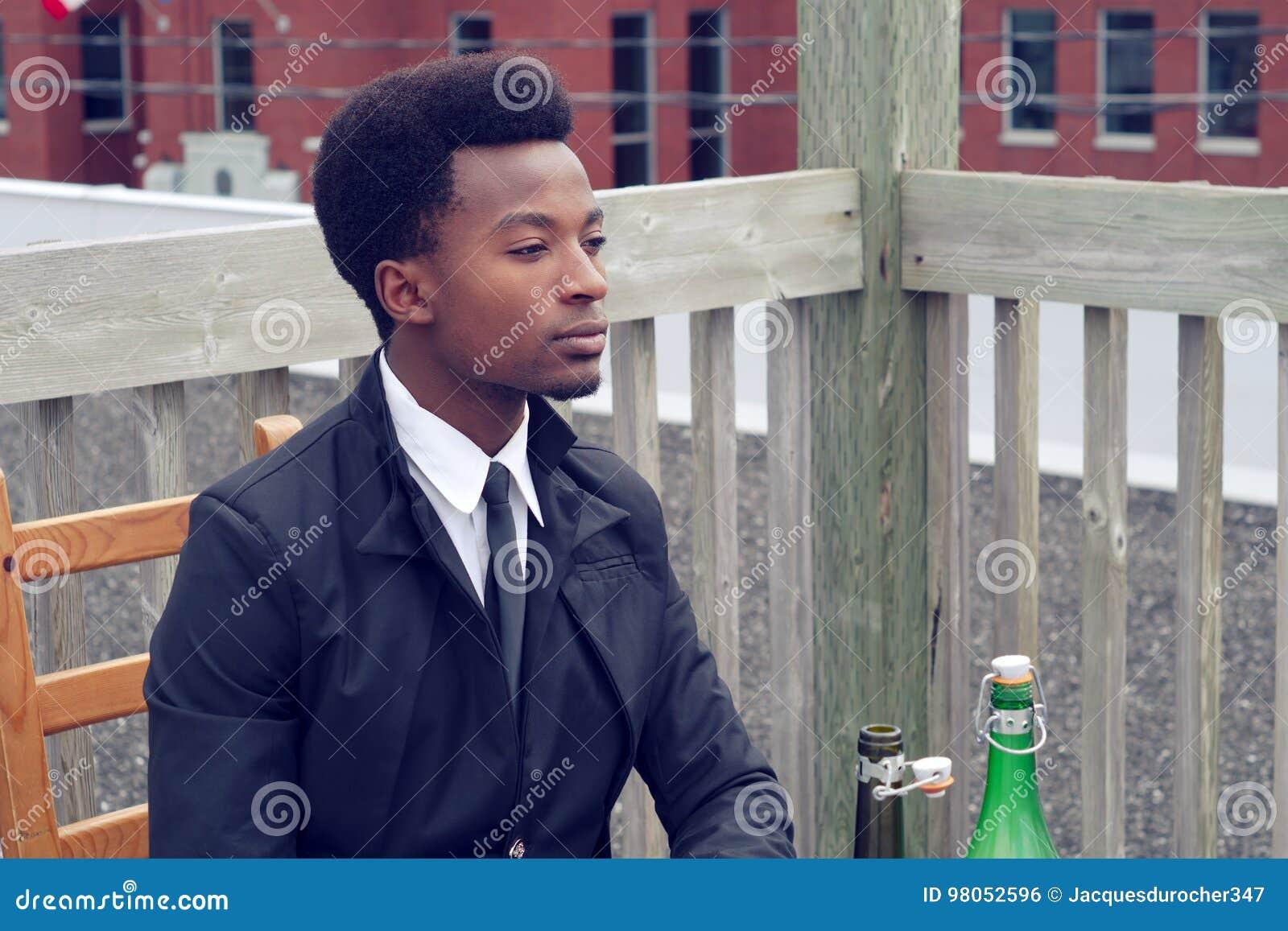 Junger Mann, der das gebohrte Restaurant datiert alleinweinflasche wartet und trinkt.