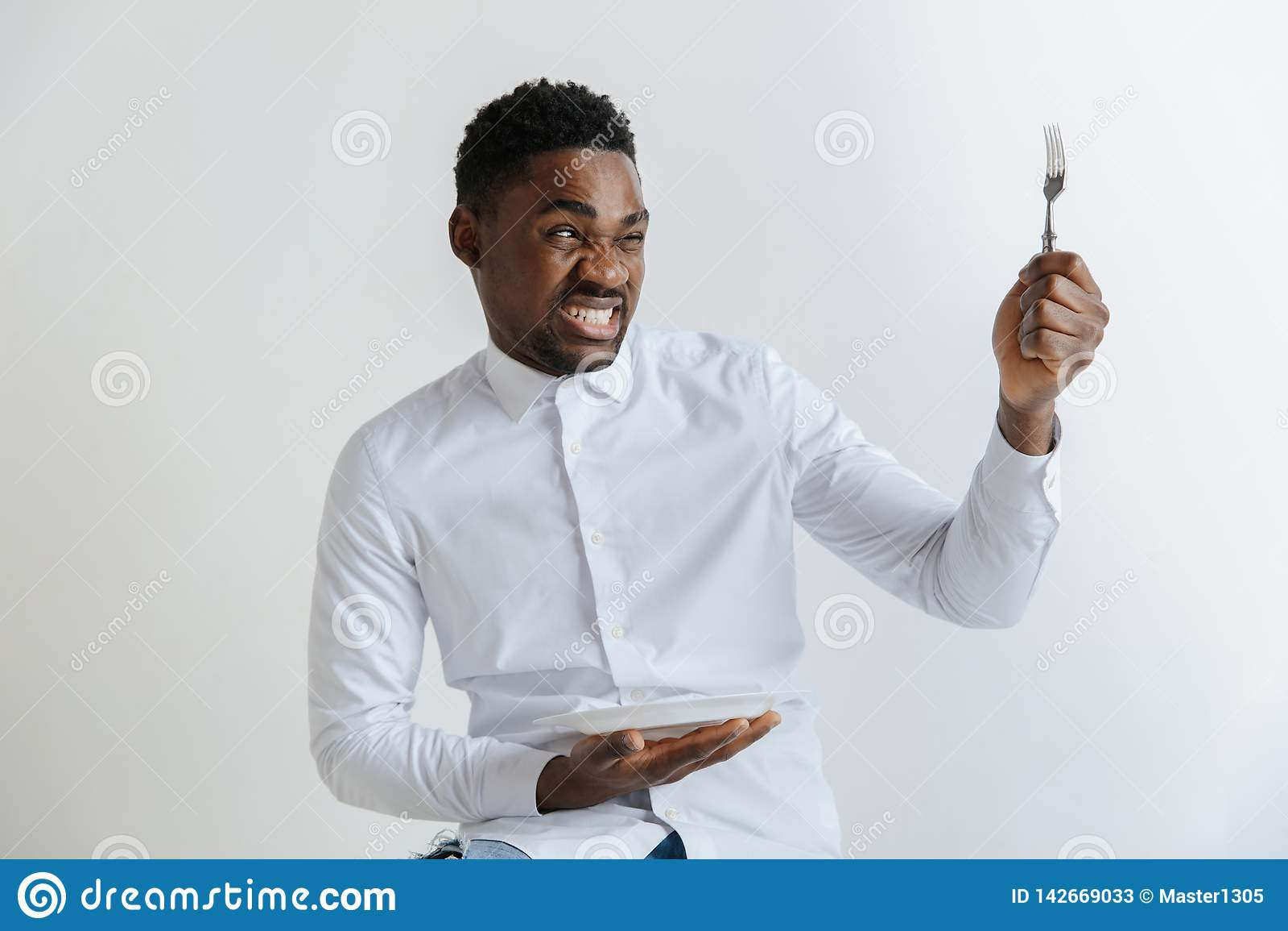 Junger Afroamerikanerkerl, der leeren Teller und die Gabel mit dem Ekeln des Gesichtsausdrucks lokalisiert auf grauem Hintergrund