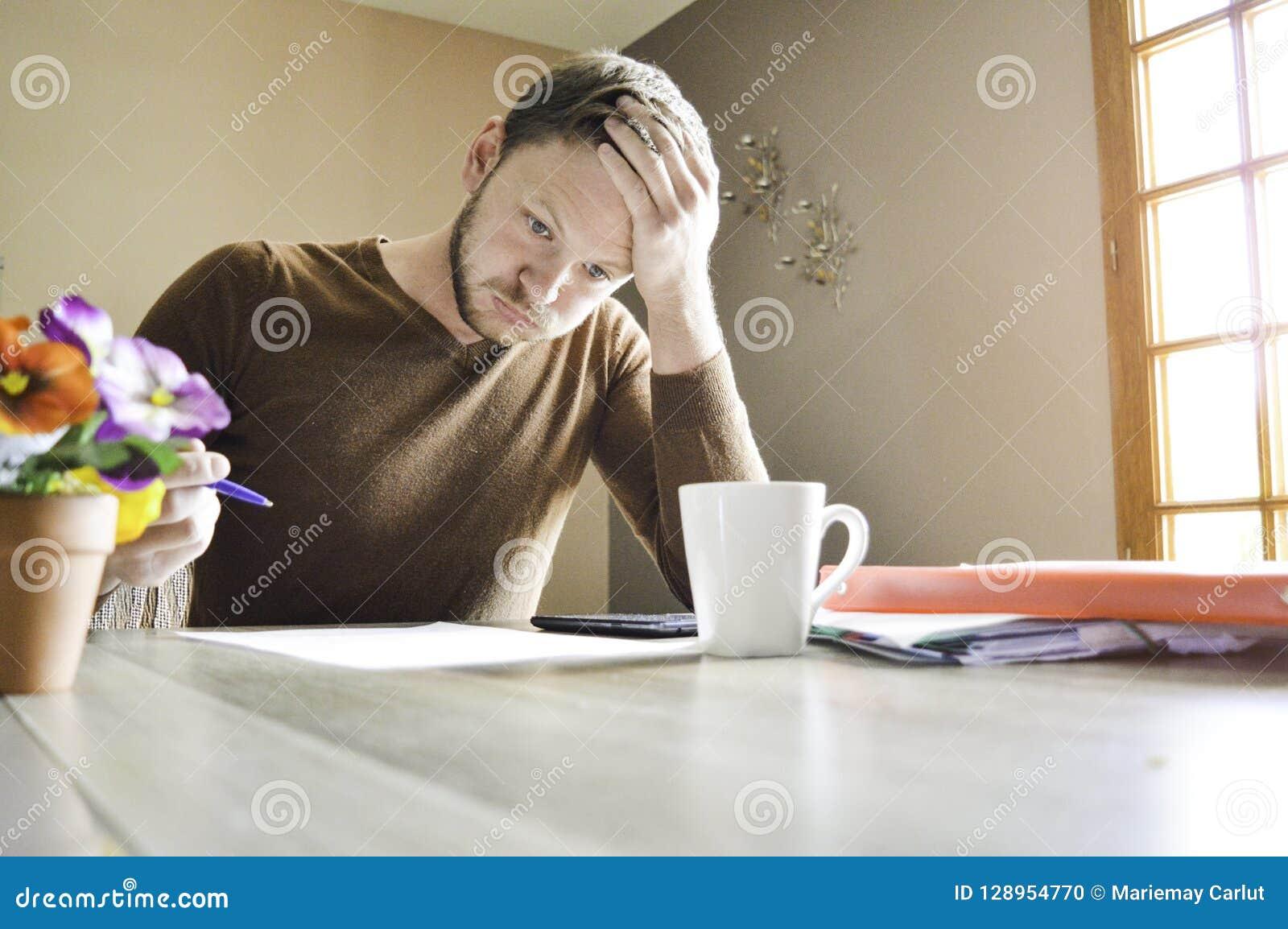 Junger aktiver Mann, der seinen Kopf stark arbeitet an Schreibarbeit am Schreibtisch hält