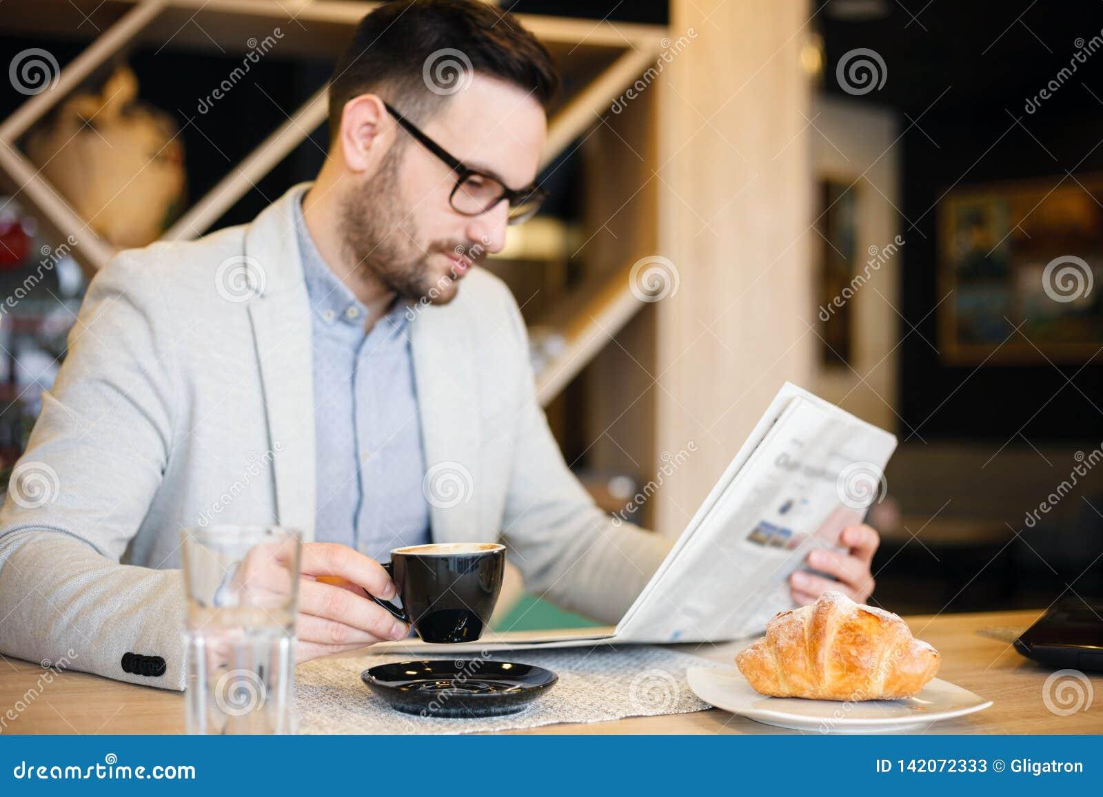 Junger Architekt, der Zeitungen liest und Kaffee in einem modernen Café trinkt Konzept der Arbeit überall