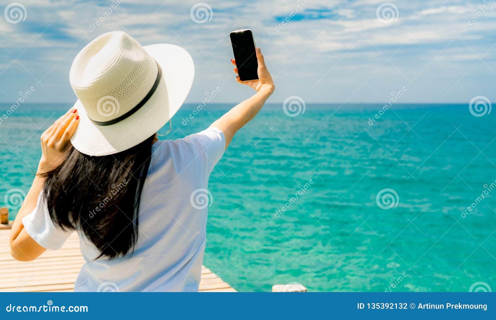 Junger Asiatinabnutzungsstrohhut in Smartphone Gebrauch der zufälligen Art, der selfie am hölzernen Pier nimmt Sommerferien am tr