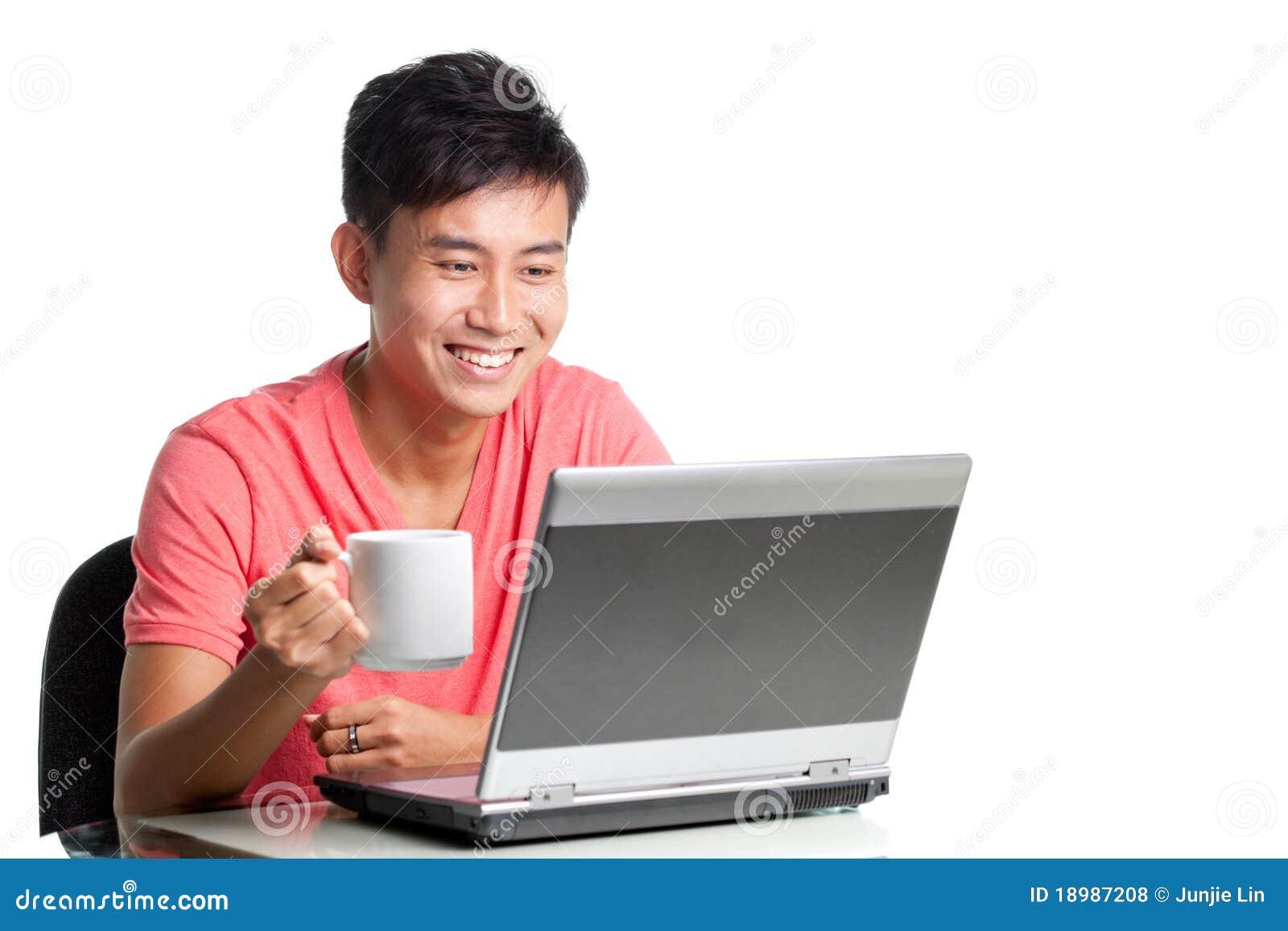 Junger asiatischer Chinese unter Verwendung des Laptops und der Entspannung