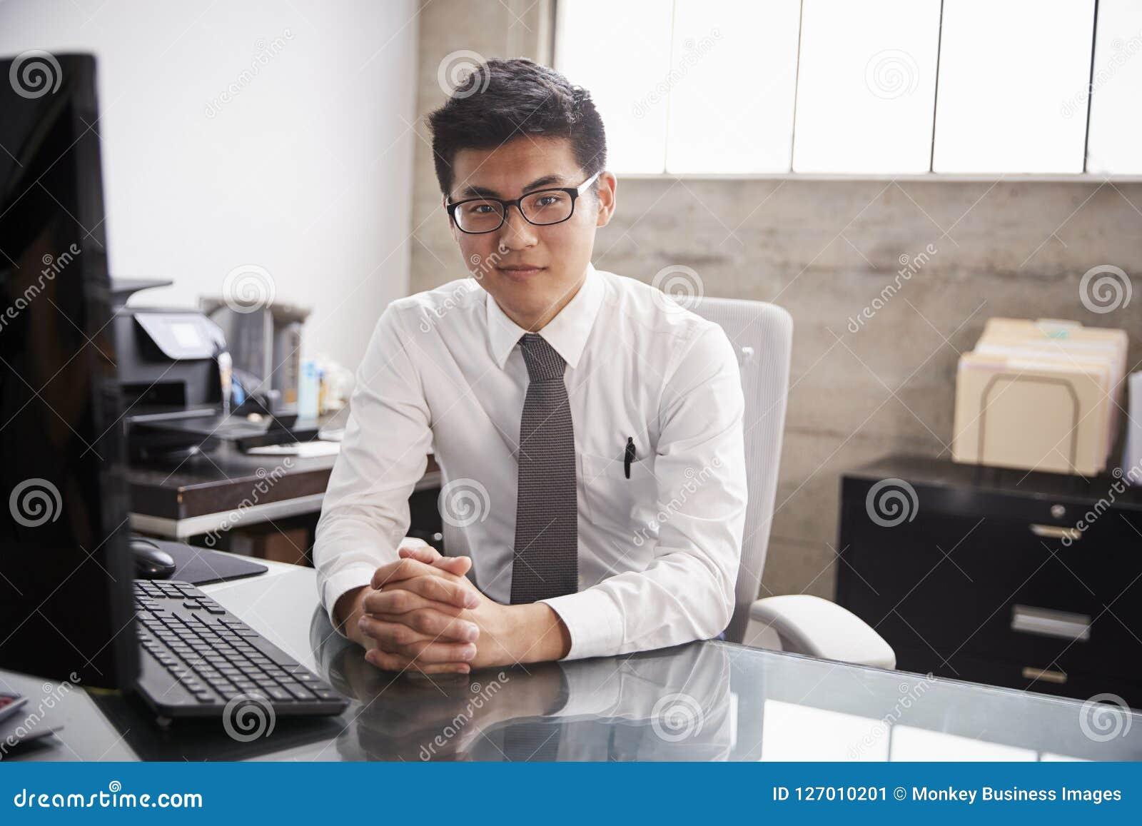 Junger asiatischer Geschäftsmann an einem Schreibtisch, schauend zur Kamera