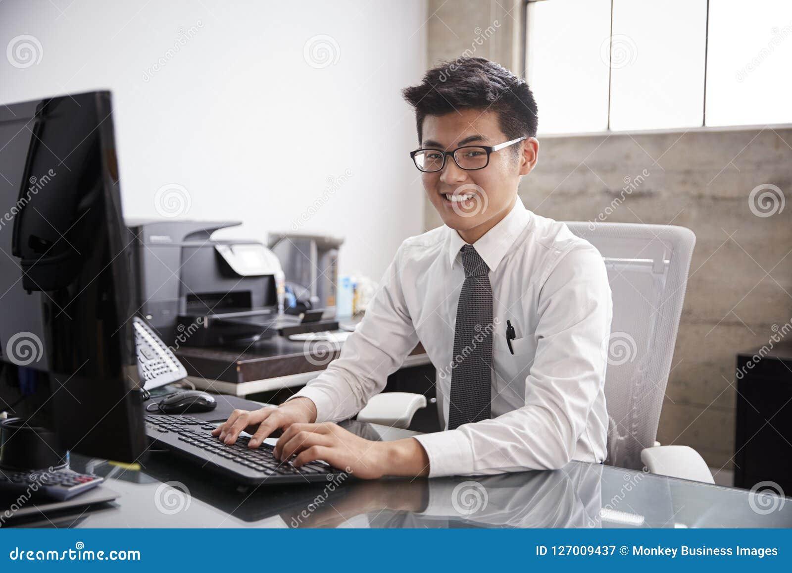 Junger asiatischer Geschäftsmann unter Verwendung eines Computers, lächelnd zur Kamera