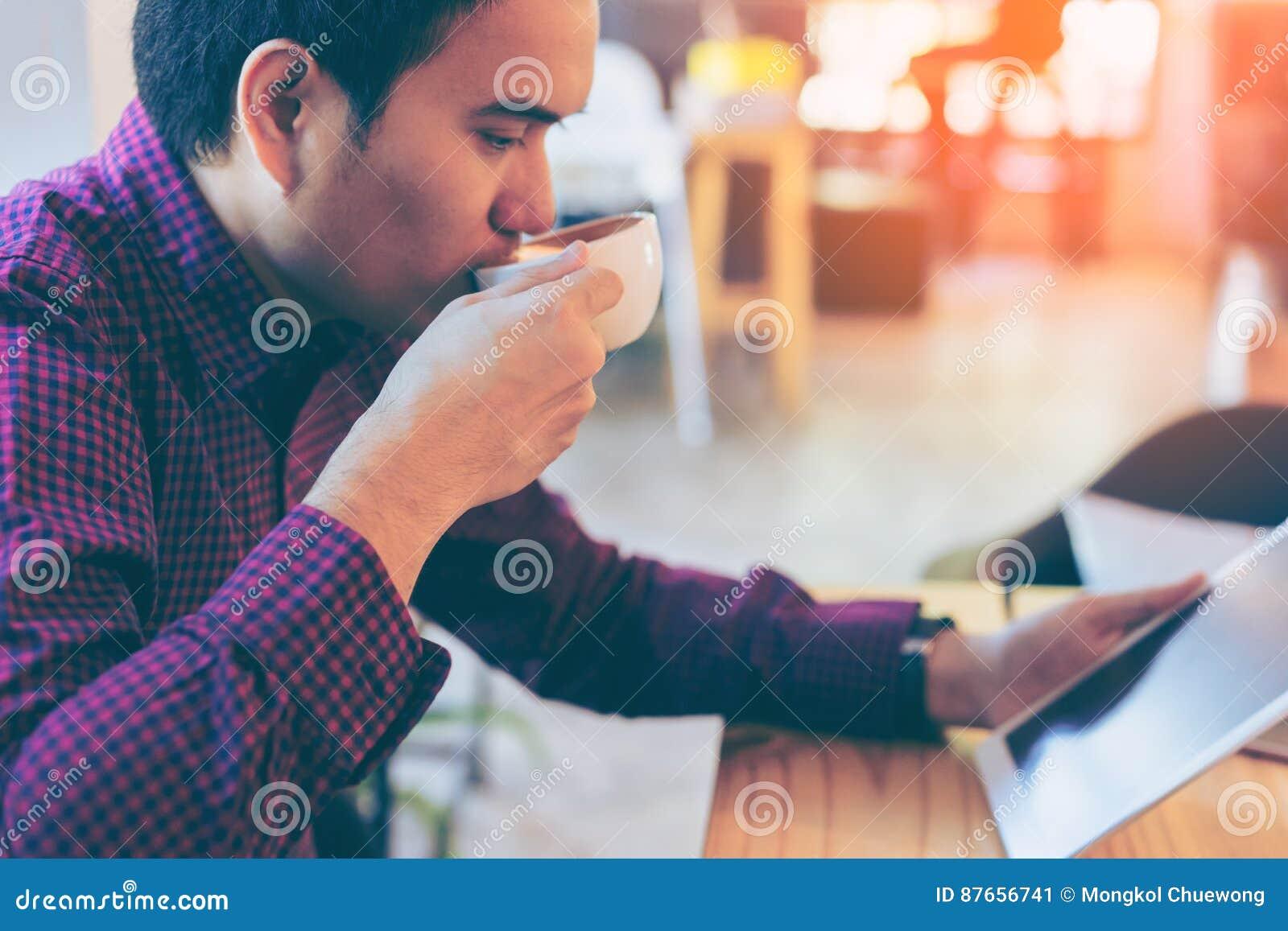 Junger asiatischer hübscher lächelnder Geschäftsmann beim Ablesen seiner Tabelle