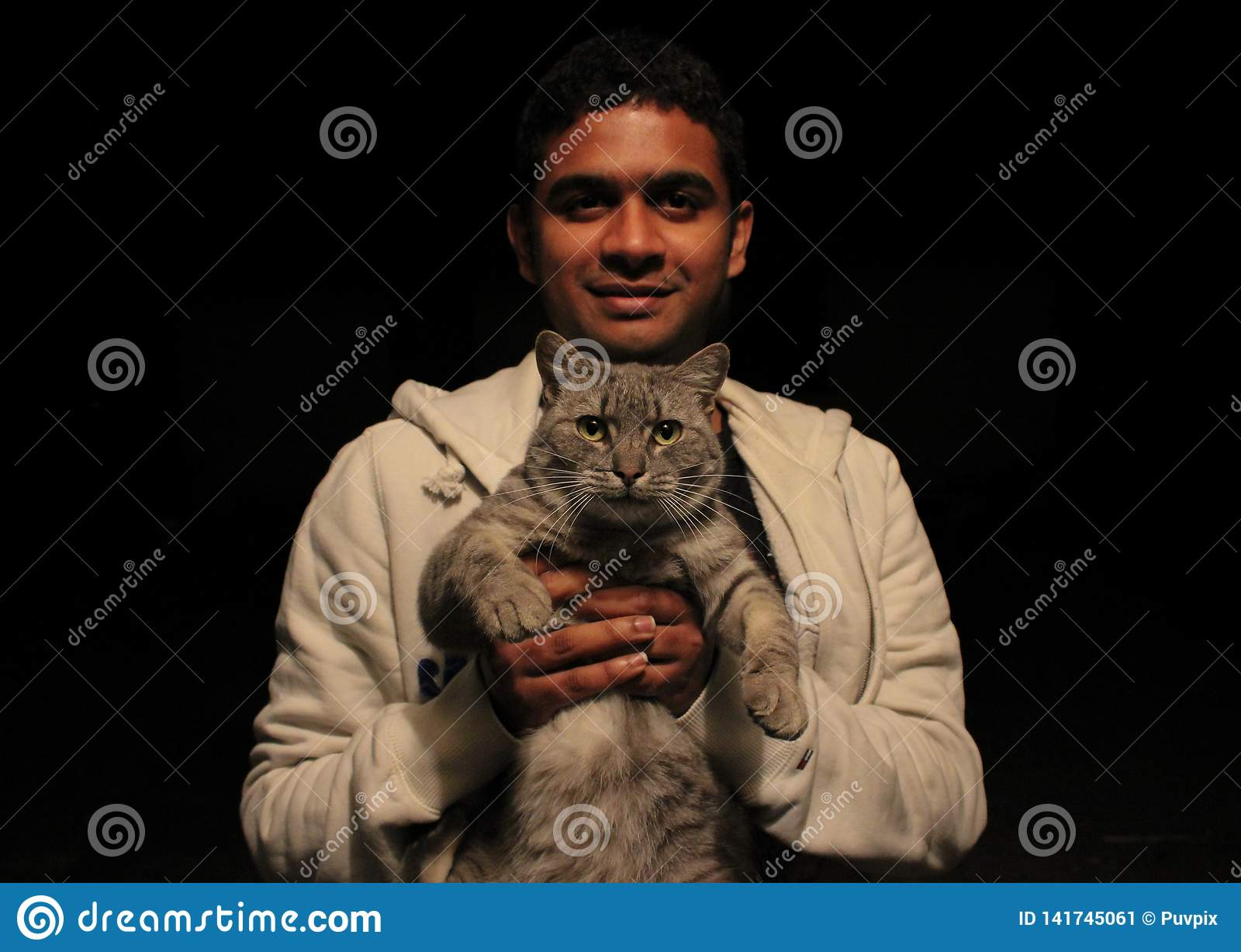 Junger asiatischer Mann, der eine Katze mit der Liebe und Lächeln, die Kamera mit einfachem schwarzem Hintergrund betrachtend häl